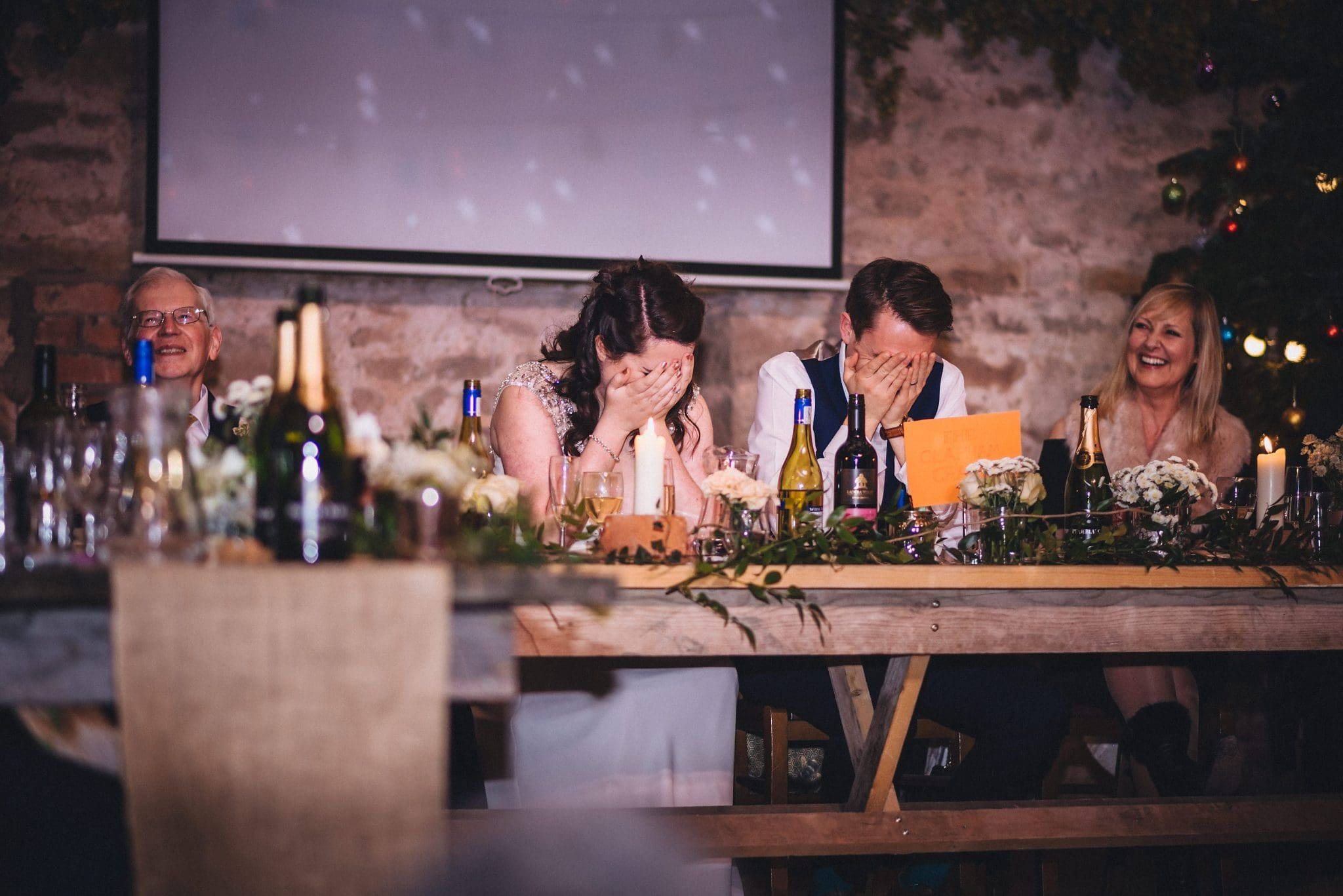 Bride and groom with their heads in their hands during one of the speeches at their Lyde Court Winter Wedding
