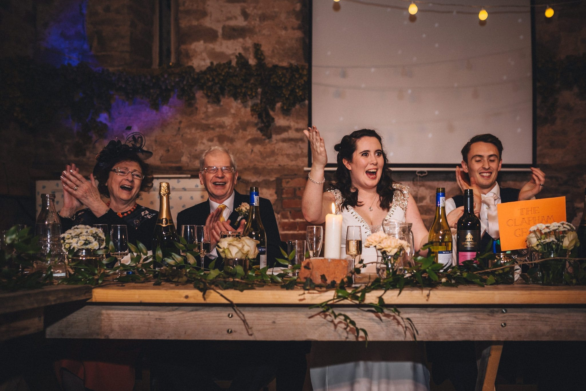 Bride gestures happily to her bridesmaids as they make a speech, rest of top table laughs and applauds