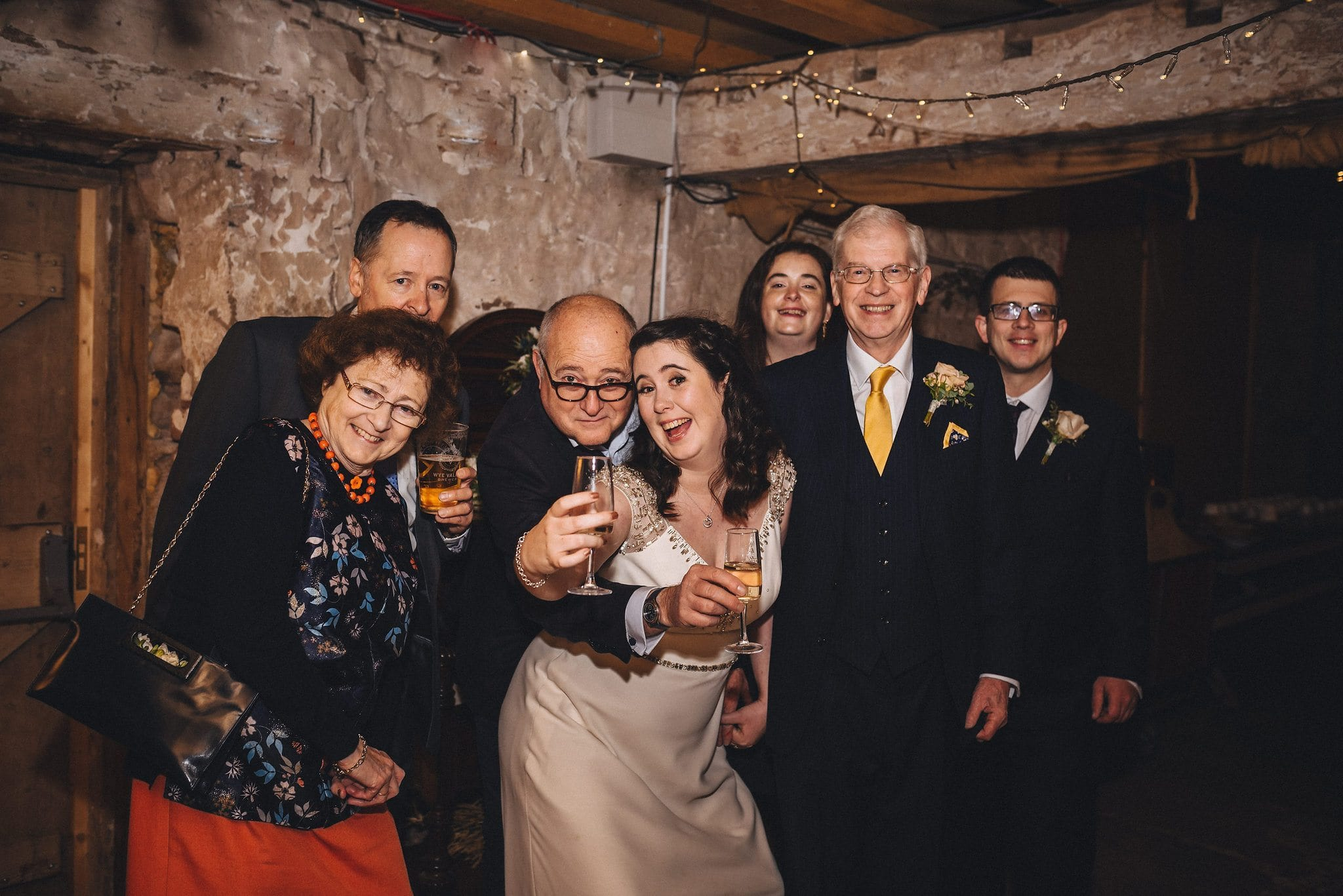 Bride poses with her family holding glasses of champagne