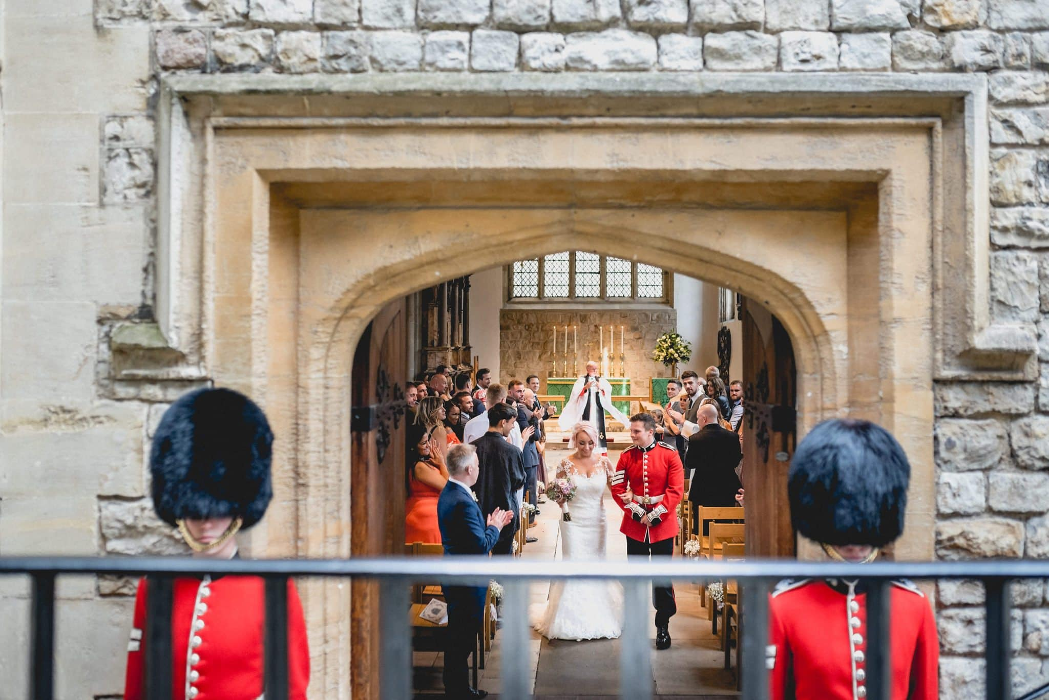 Bride and groom exit the Tower of London after their wedding ceremony. The door is guarded by two of the Royal Guard in full regalia.