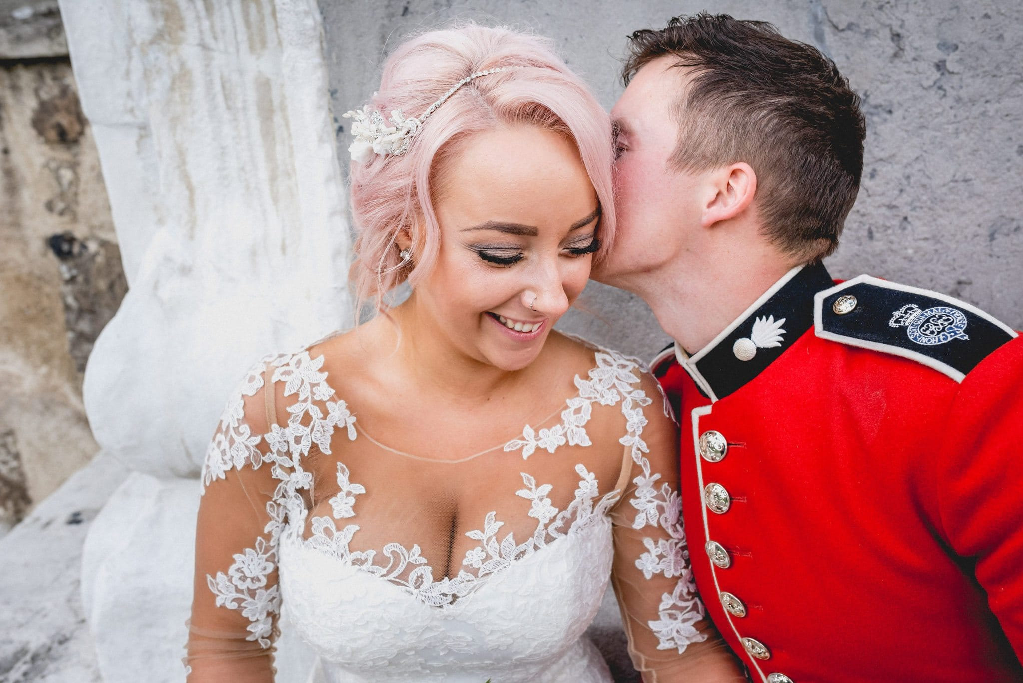 Groom kisses his beautiful bride behind the ear in their couple's shoot outside the Tower of London