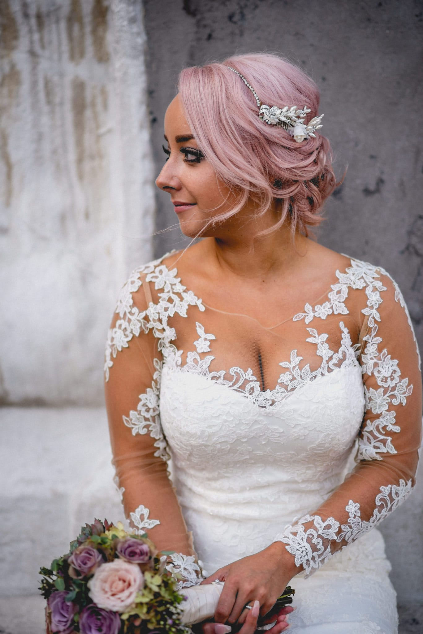 Bridal portrait of bride with pale pink hair and gown with illusion lace sleeves