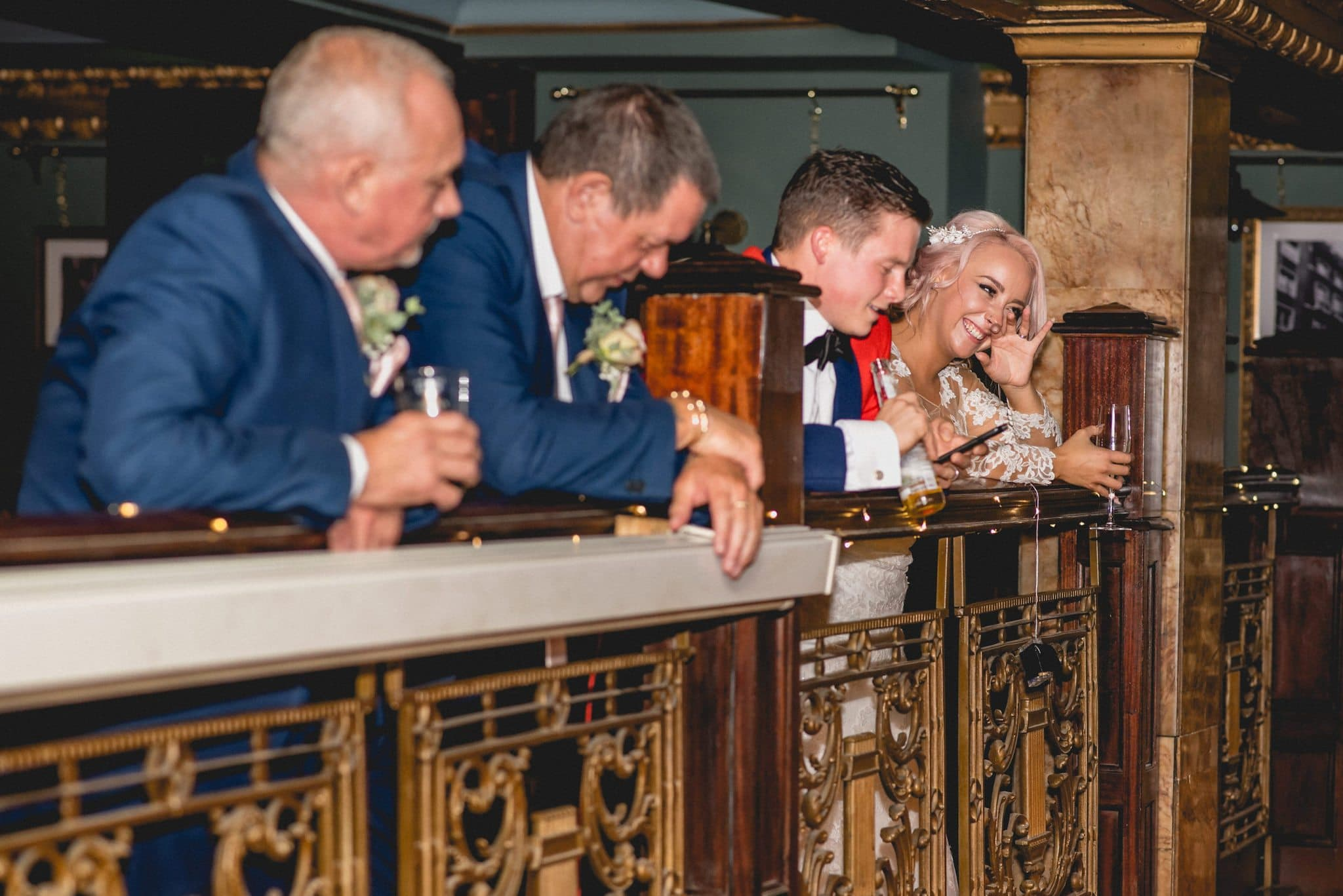 Bride and groom laugh during the speeches on the balcony of the Counting House pub