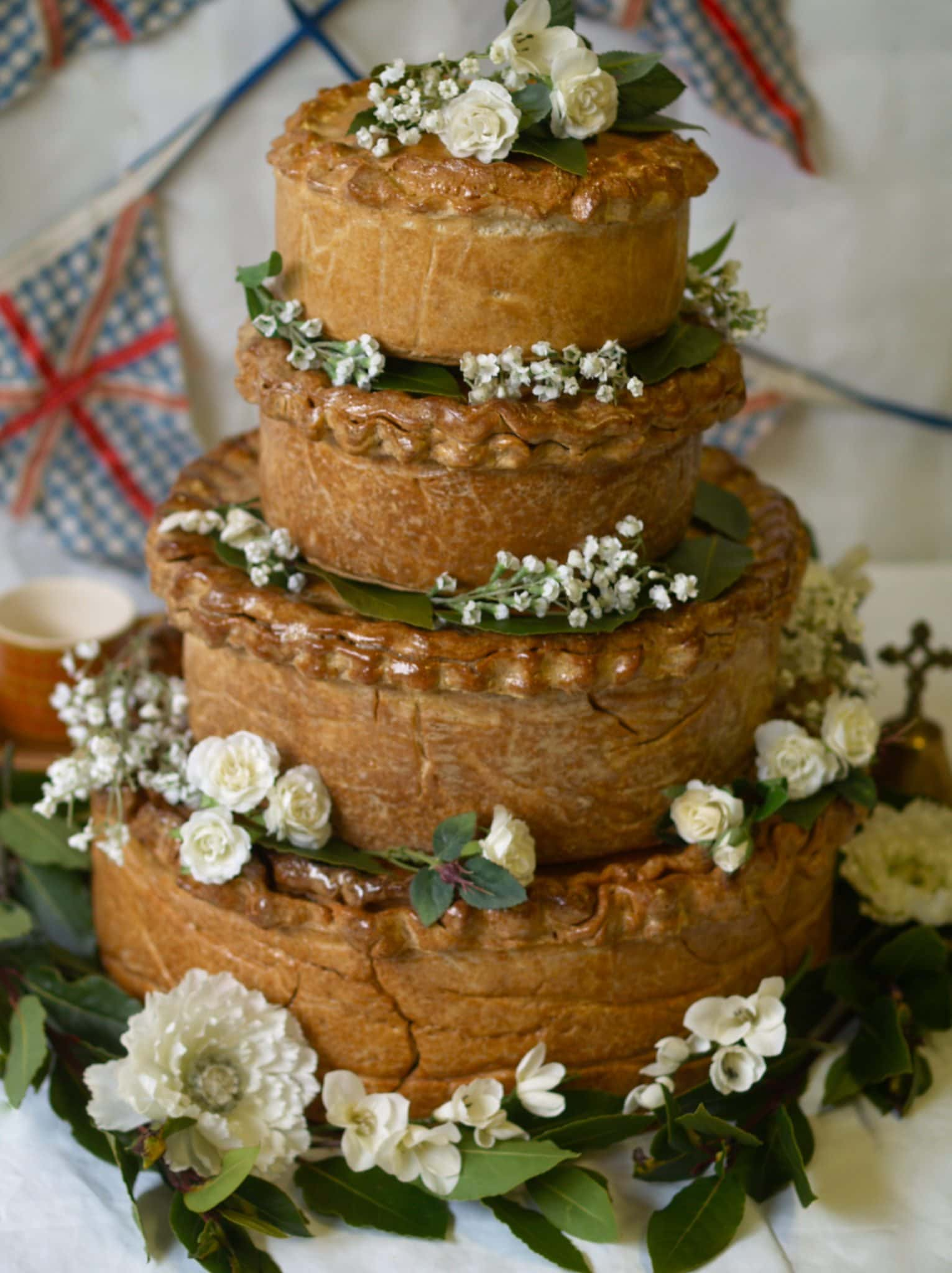 Tiered pork pie decorated with flowers - a savoury alternative to your wedding cake.