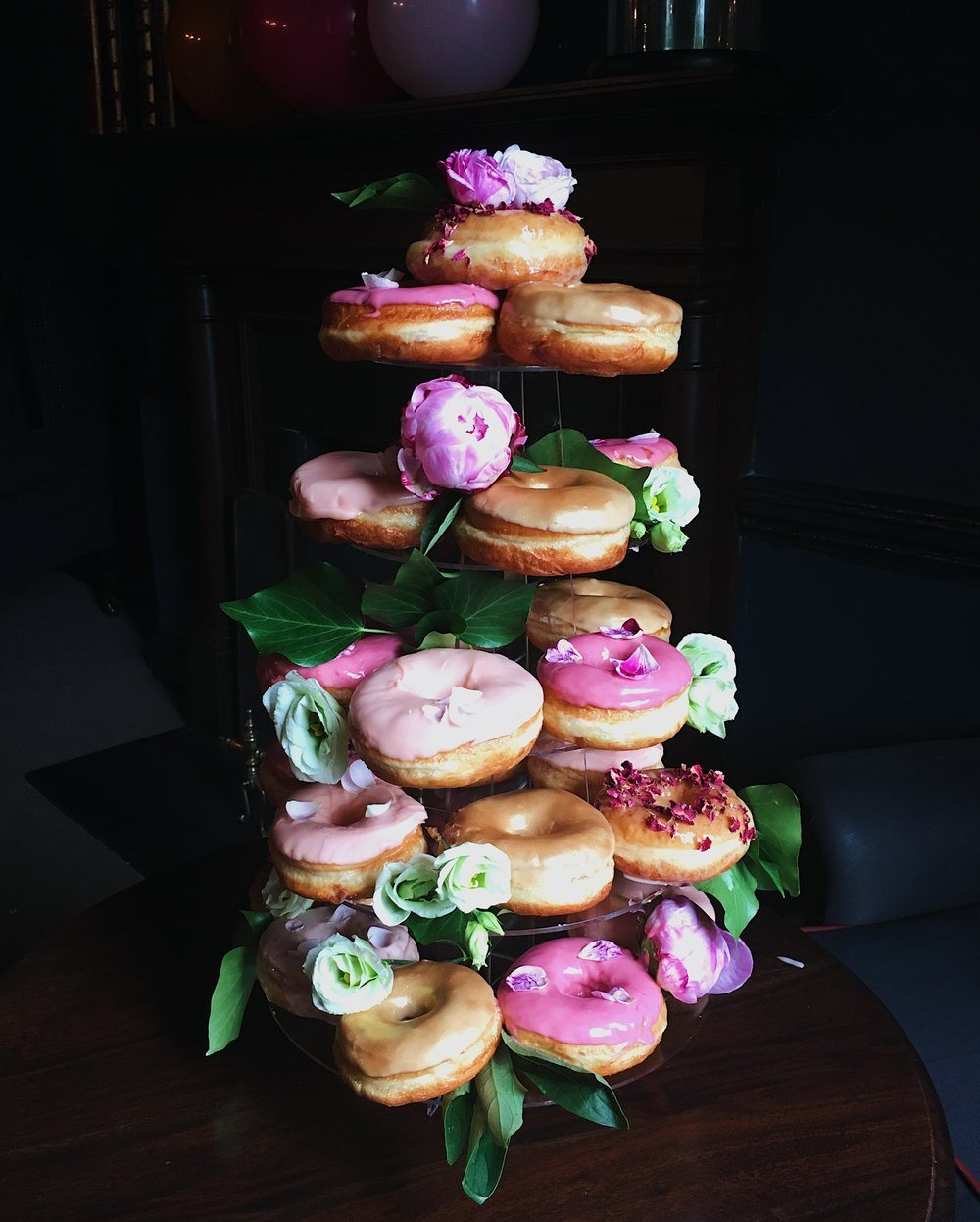 A tower of glazed ring donuts with glaze in different shades of pink.