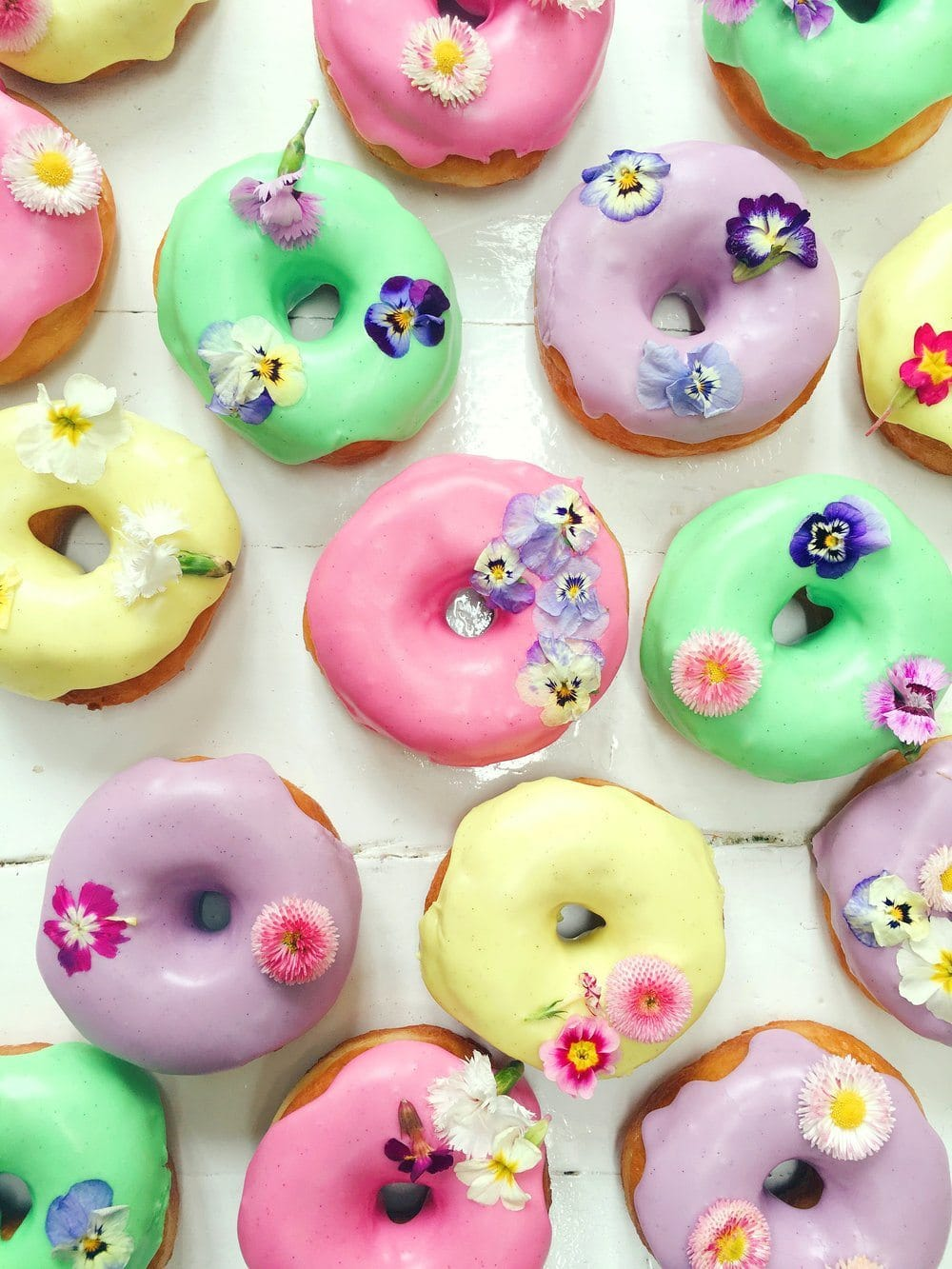 Ring donuts from Vicky's Donuts iced in bright colours and decorated with edible flowers