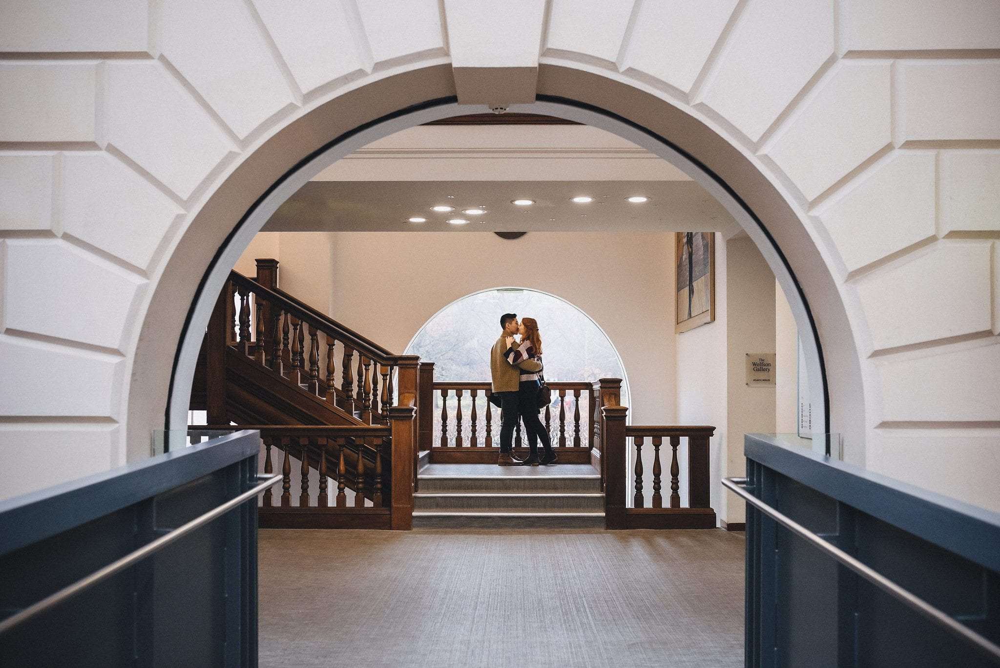 Engaged couple kissing in front of a large rounded window