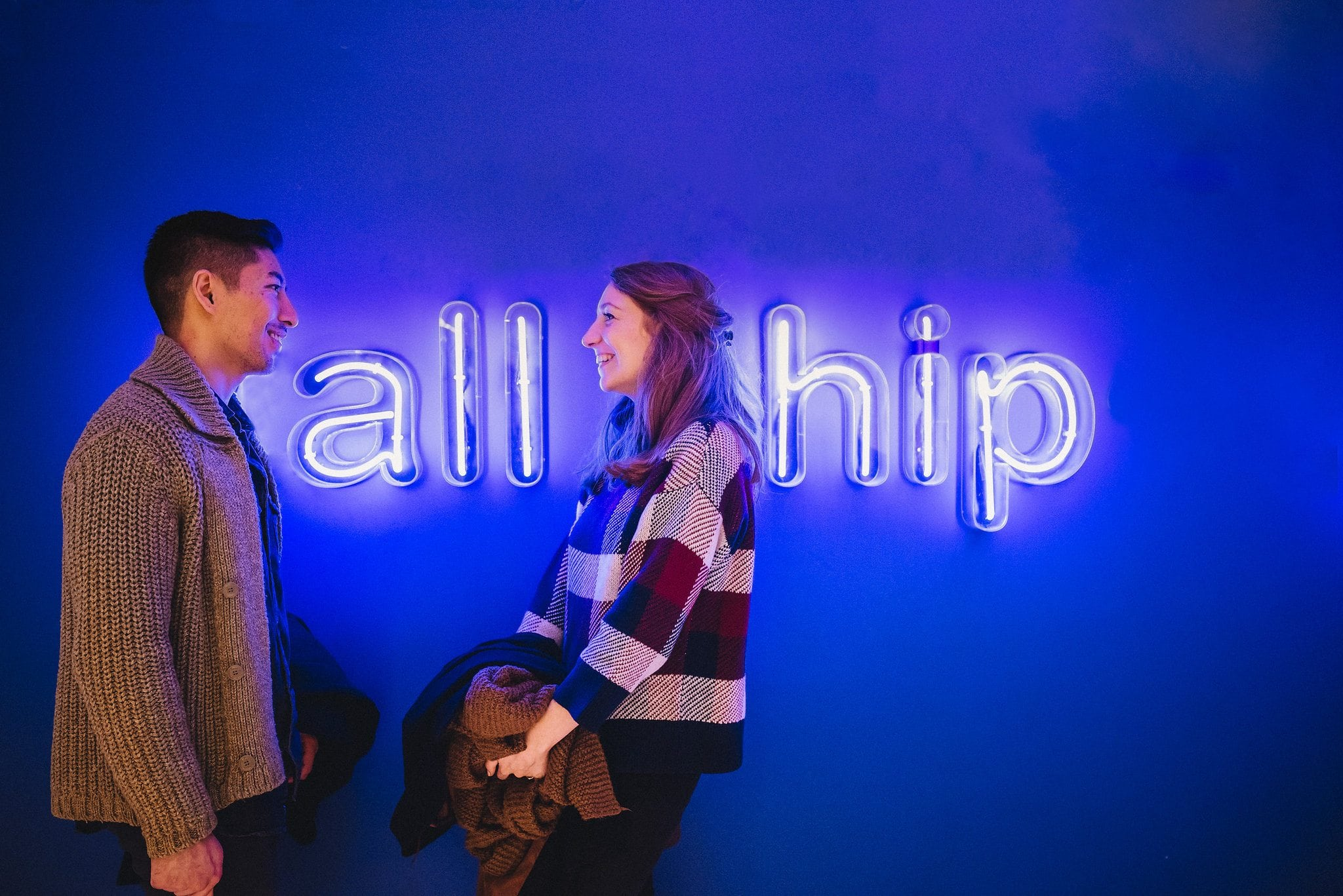 Couple standing in front of a blue neon sign which reads all hip