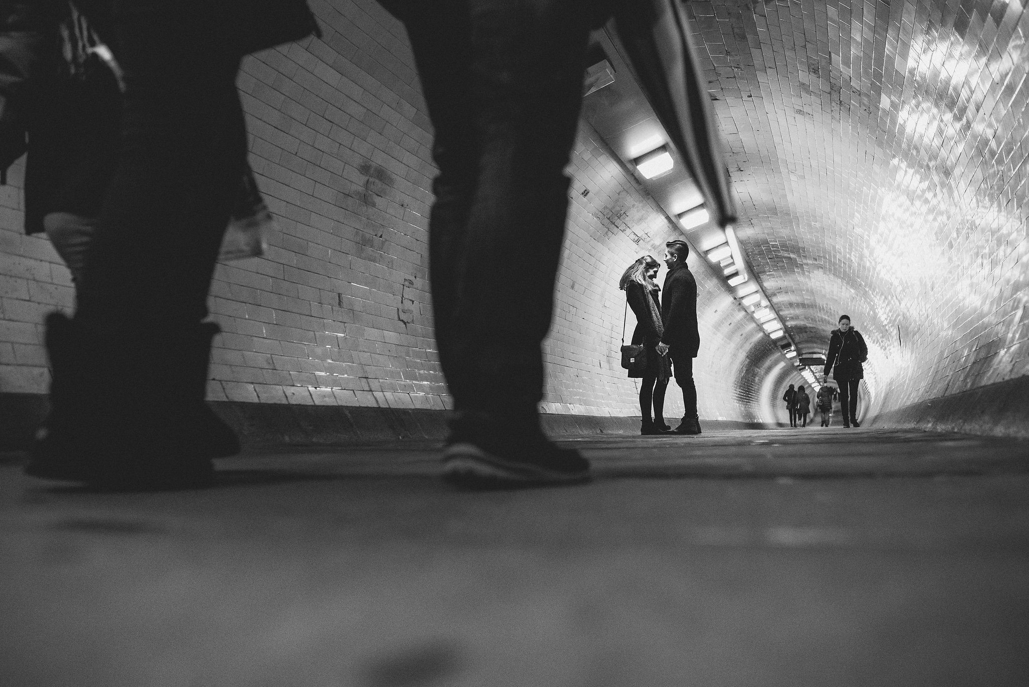 engaged couple holding hands in the Greenwhich foot tunnel while people walk by