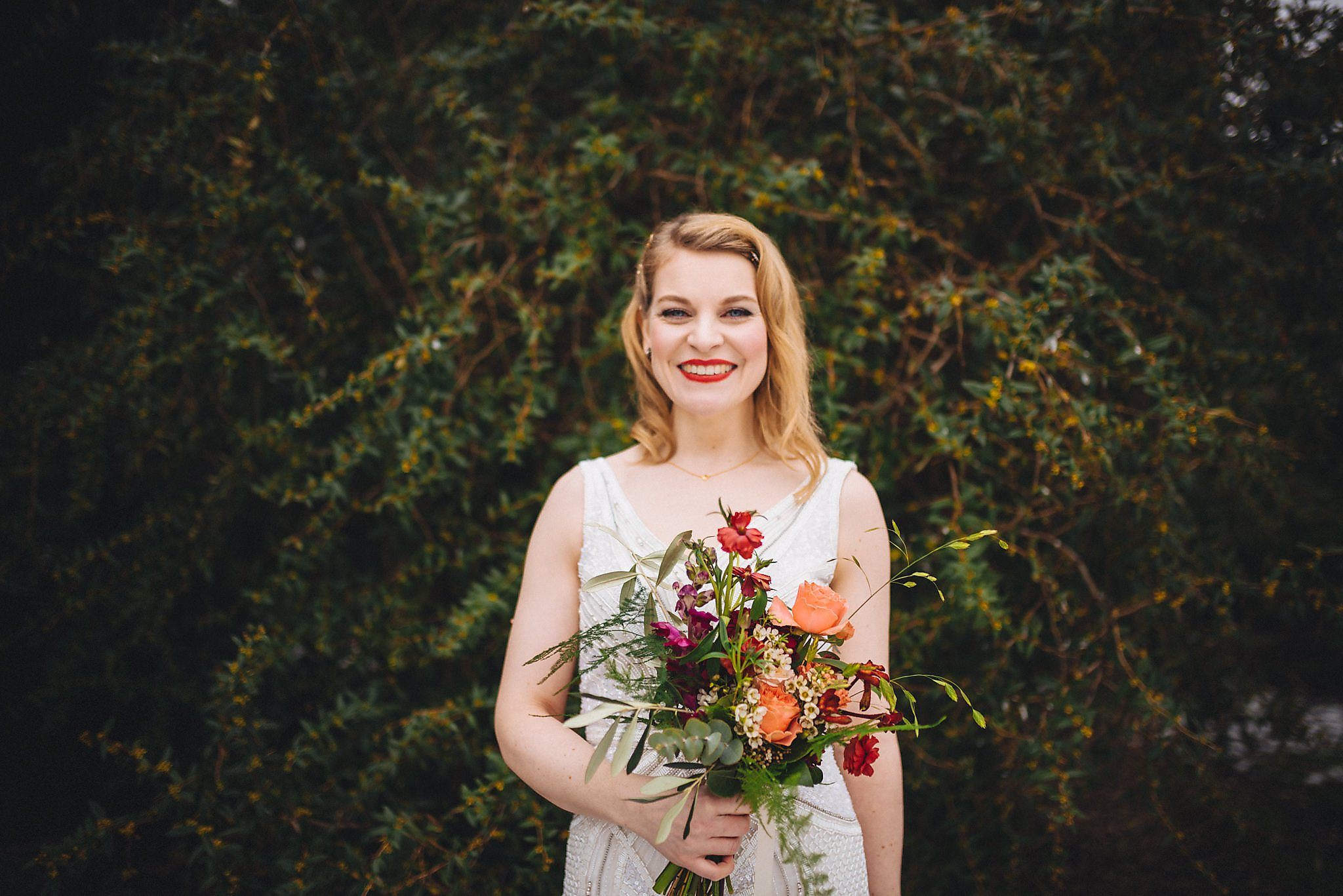 Bride in sequinned wedding gown poses with bouquet