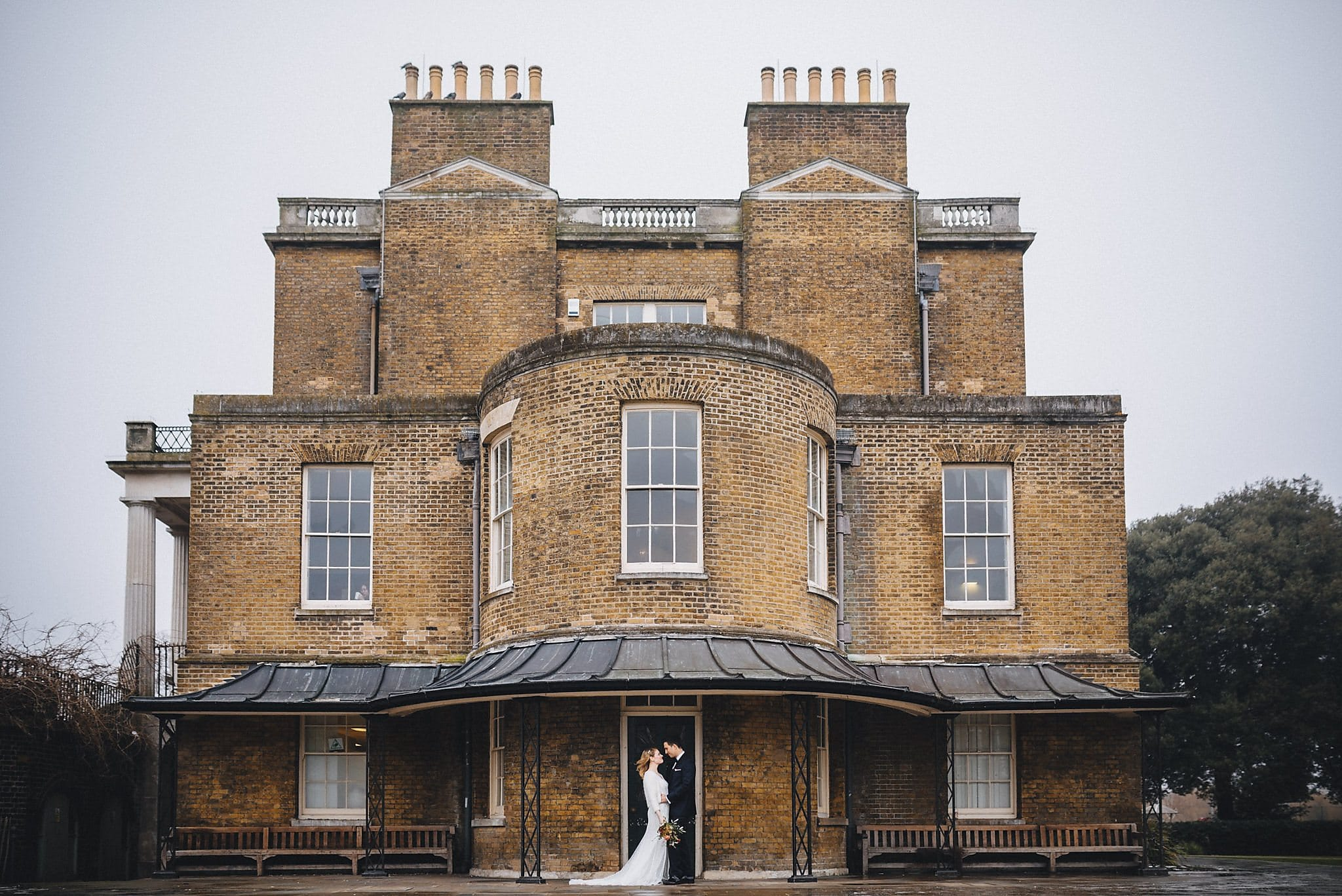Bride and groom standing in front of Clissold House for their wedding