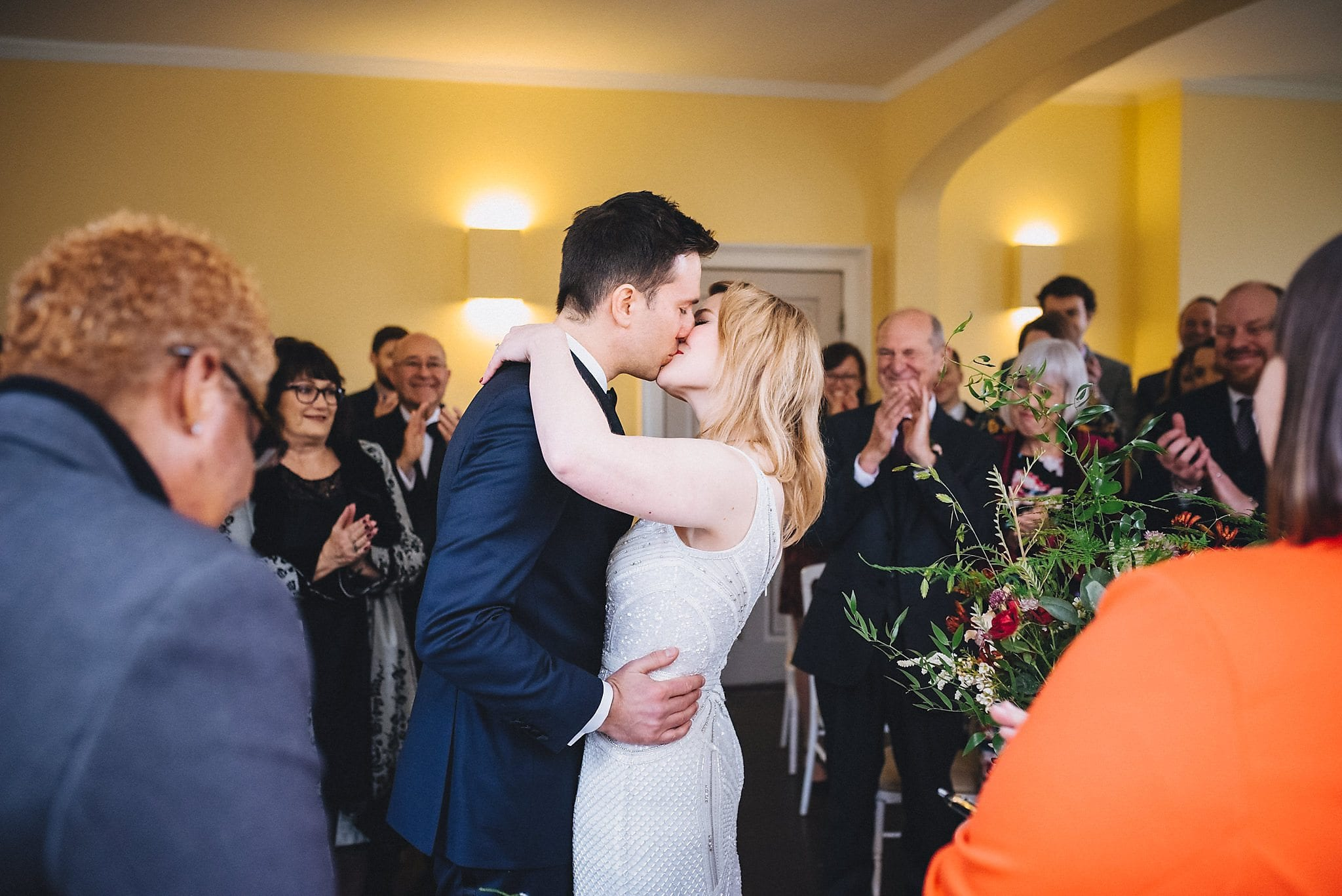 Bride and groom kiss at wedding ceremony in Clissold House
