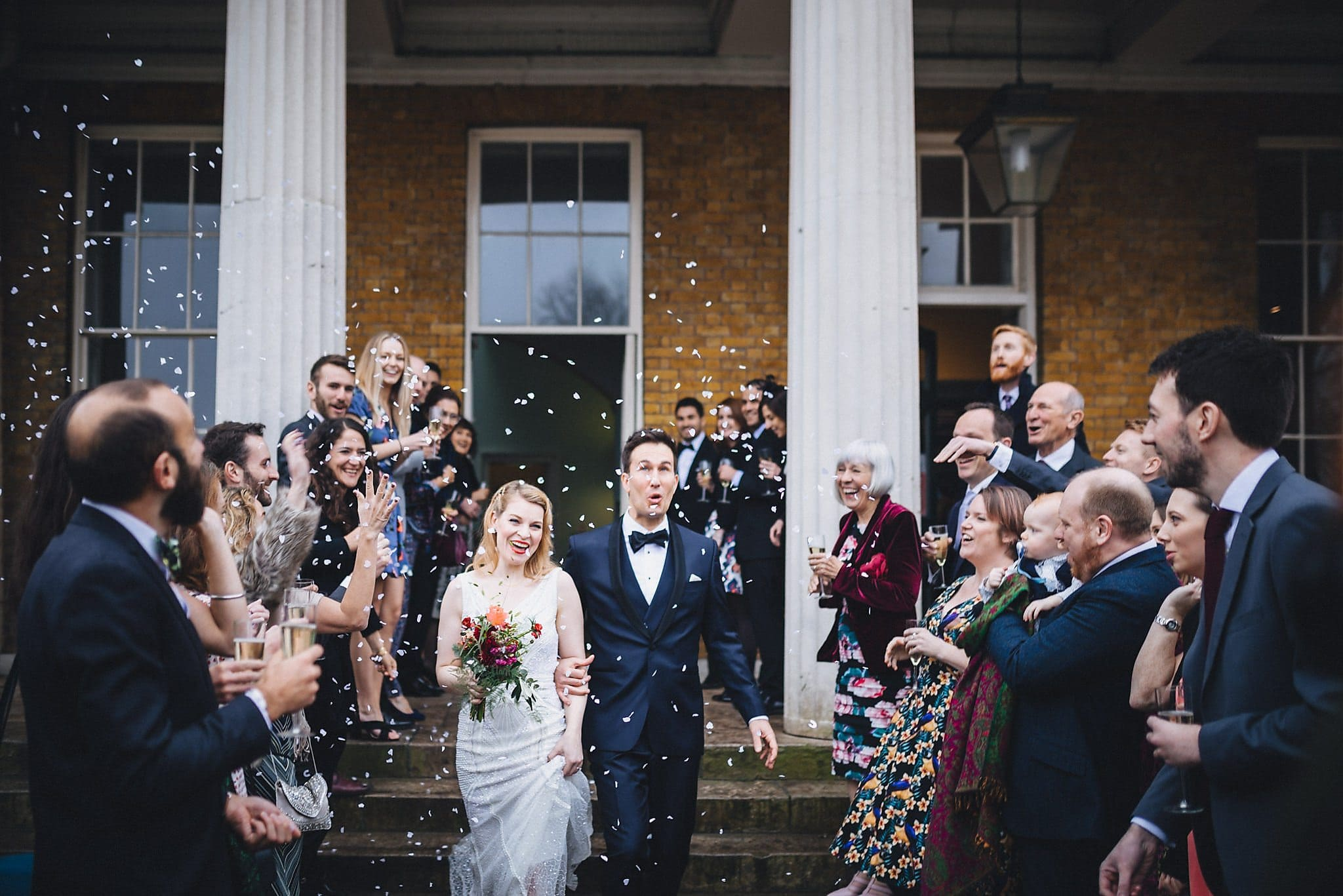 Bride and groom walk through white confetti at Clissold House
