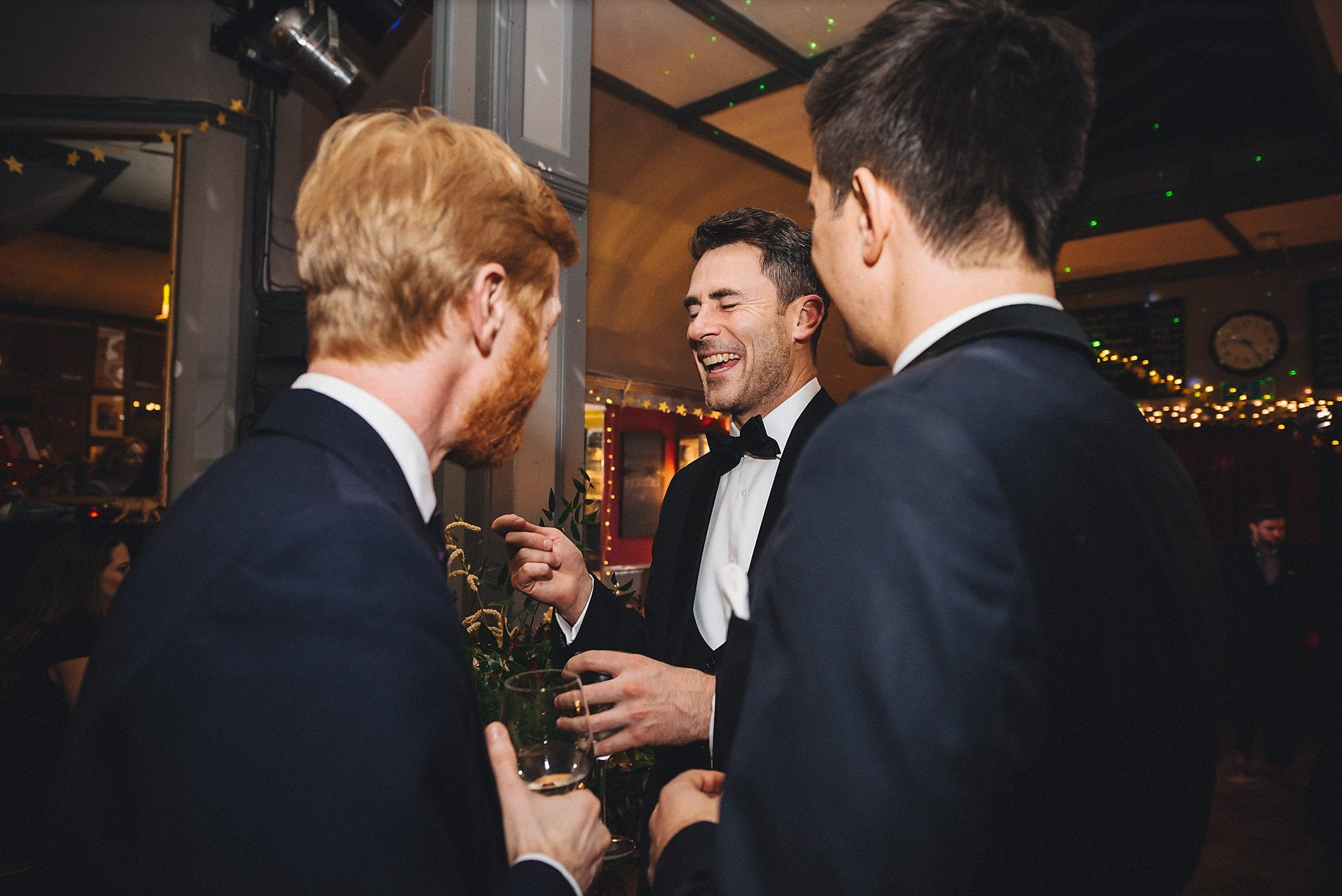 Groom laughing with guests at reception