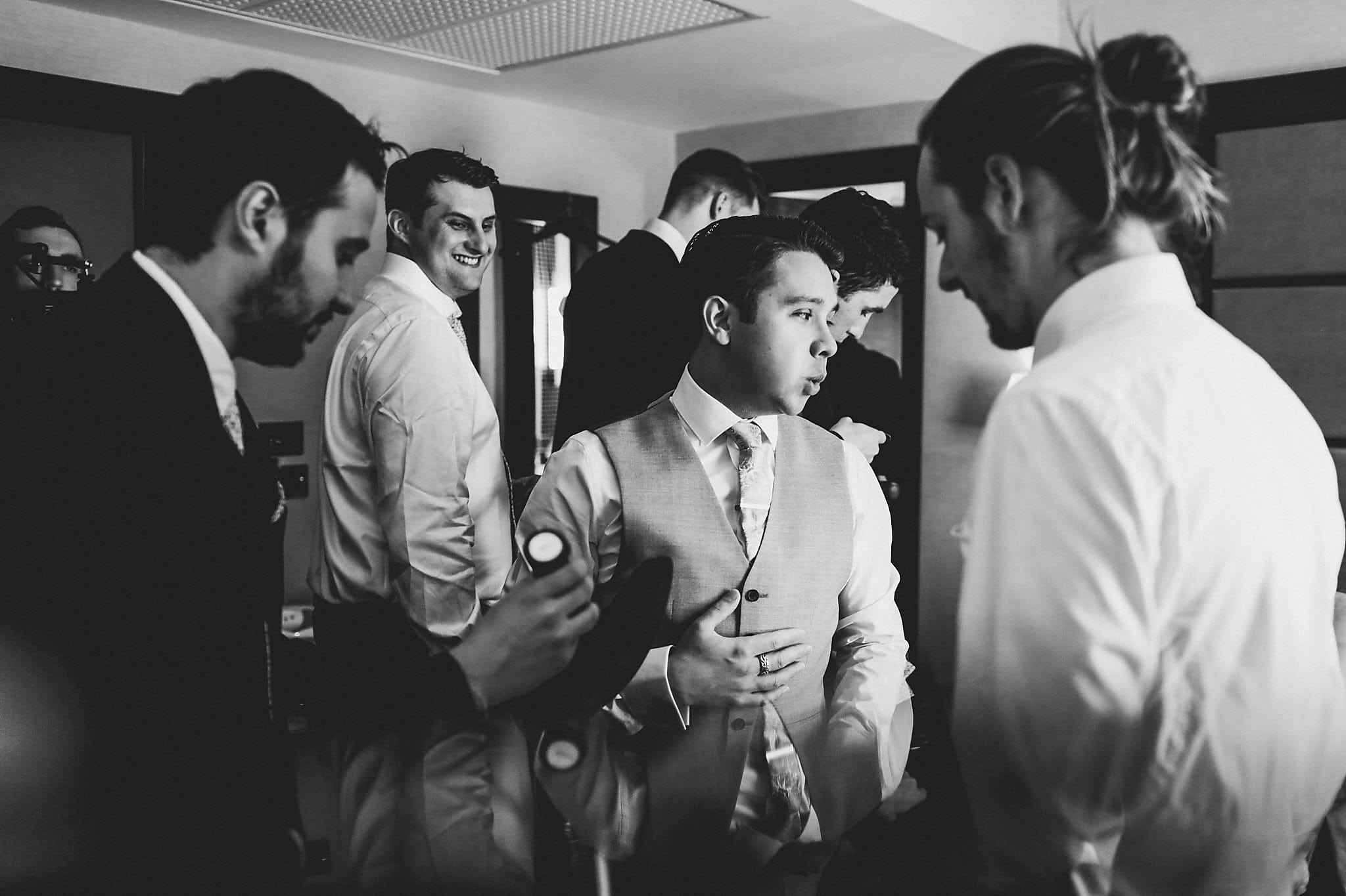 Black and white shot of groom and groomsmen getting ready