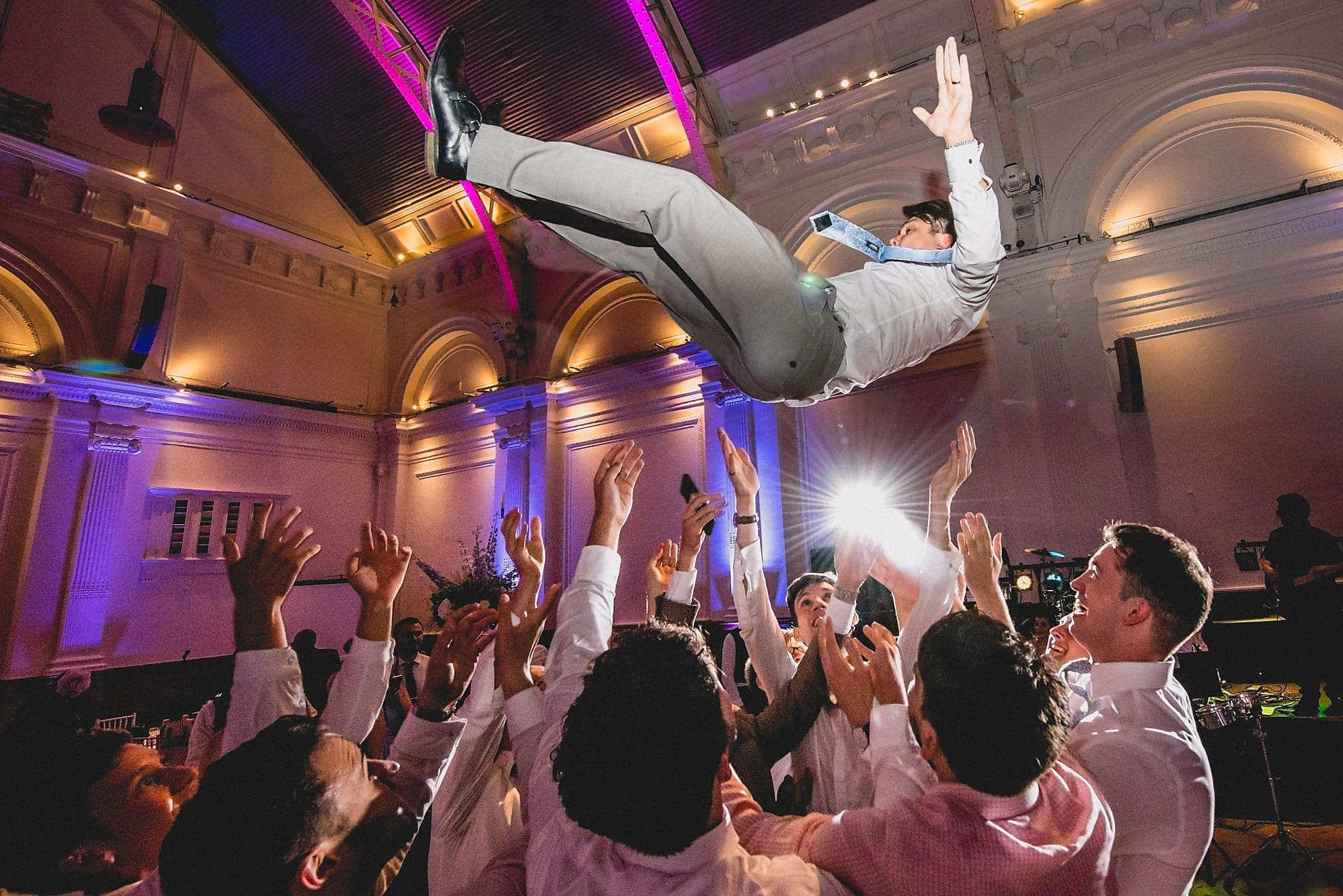 Groom is thrown into the air during the boys dance at his modern Greek wedding
