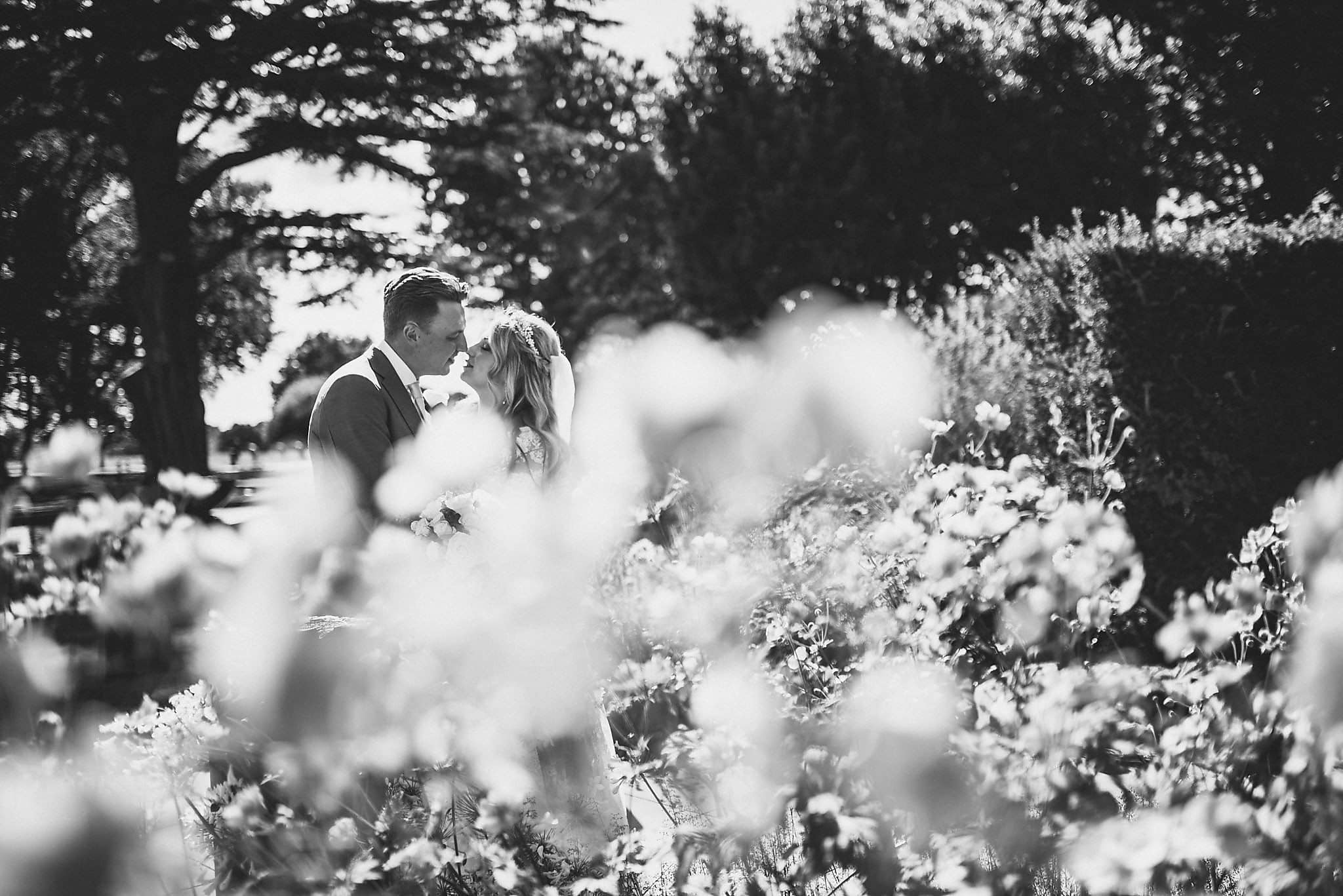Bride and Groom kiss among pink blossom in the gardens at The Grove