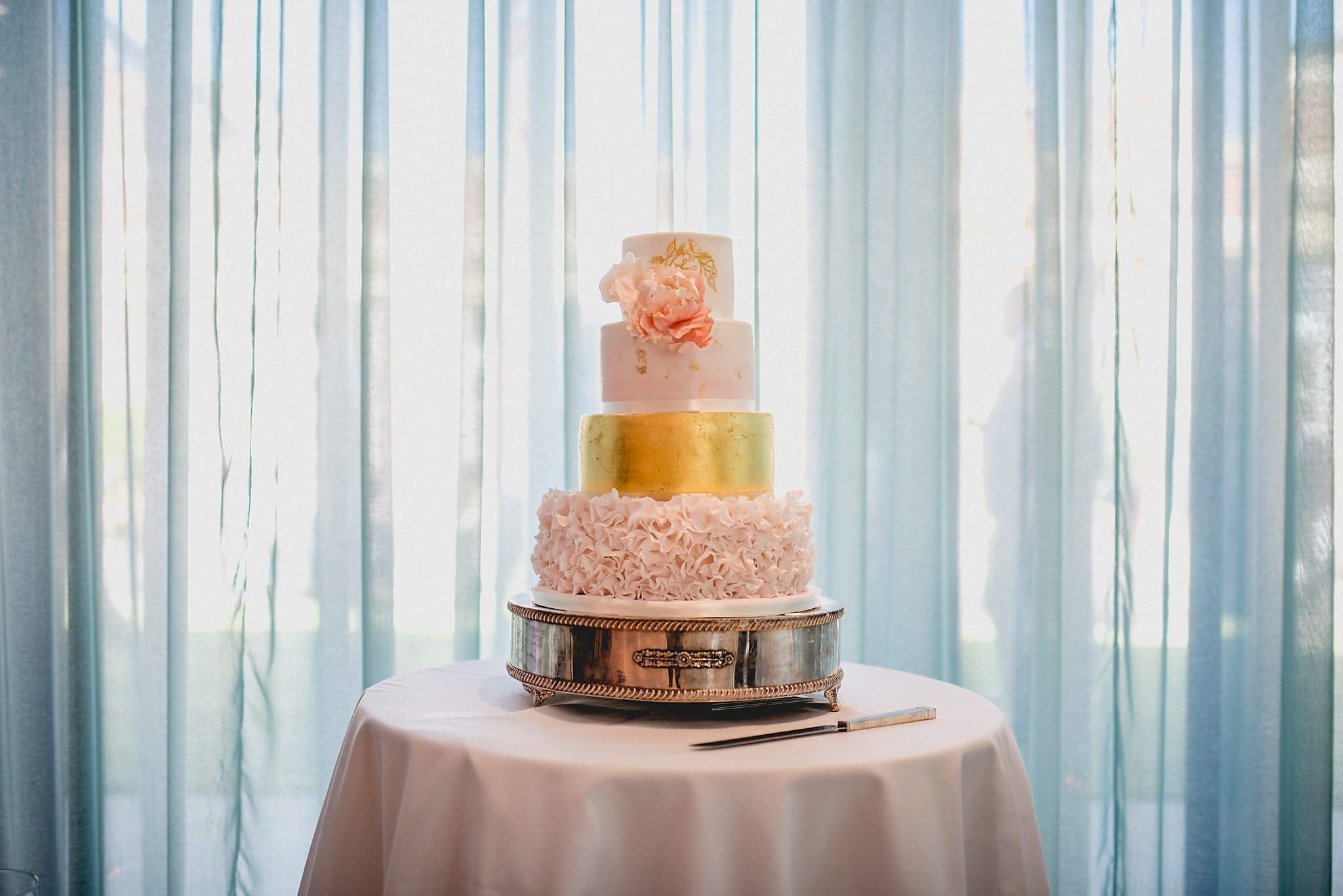 Beautiful gold and peach wedding cake at The Grove Wedding