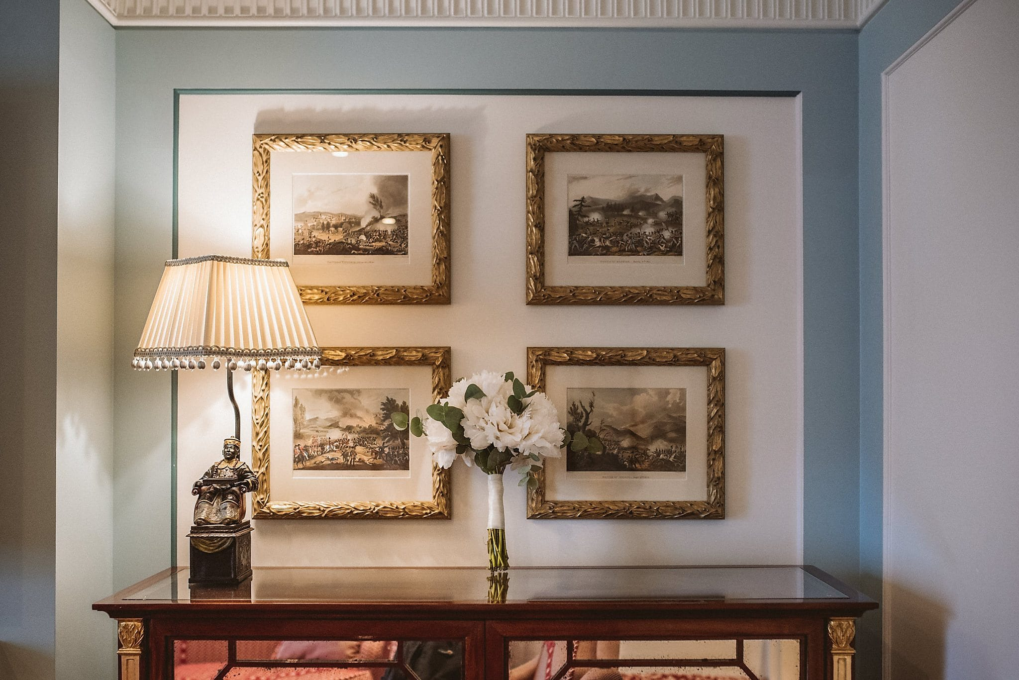 Bridal bouquet on table with gilt framed pictures on the wall behind it