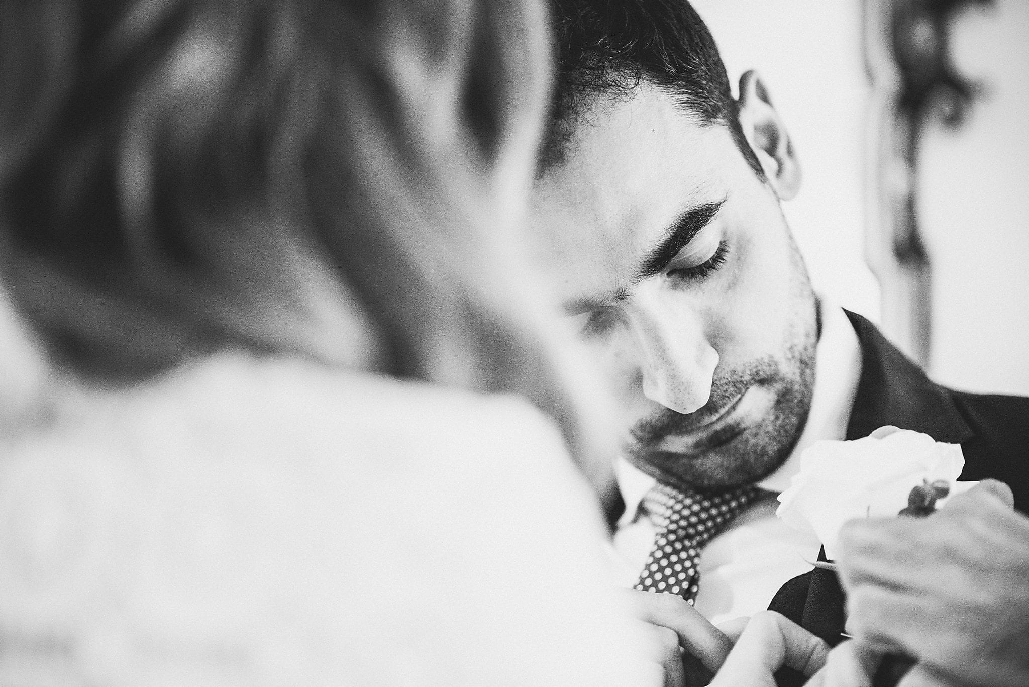 Black and white shot of the bride adjusting the groom's buttonhole