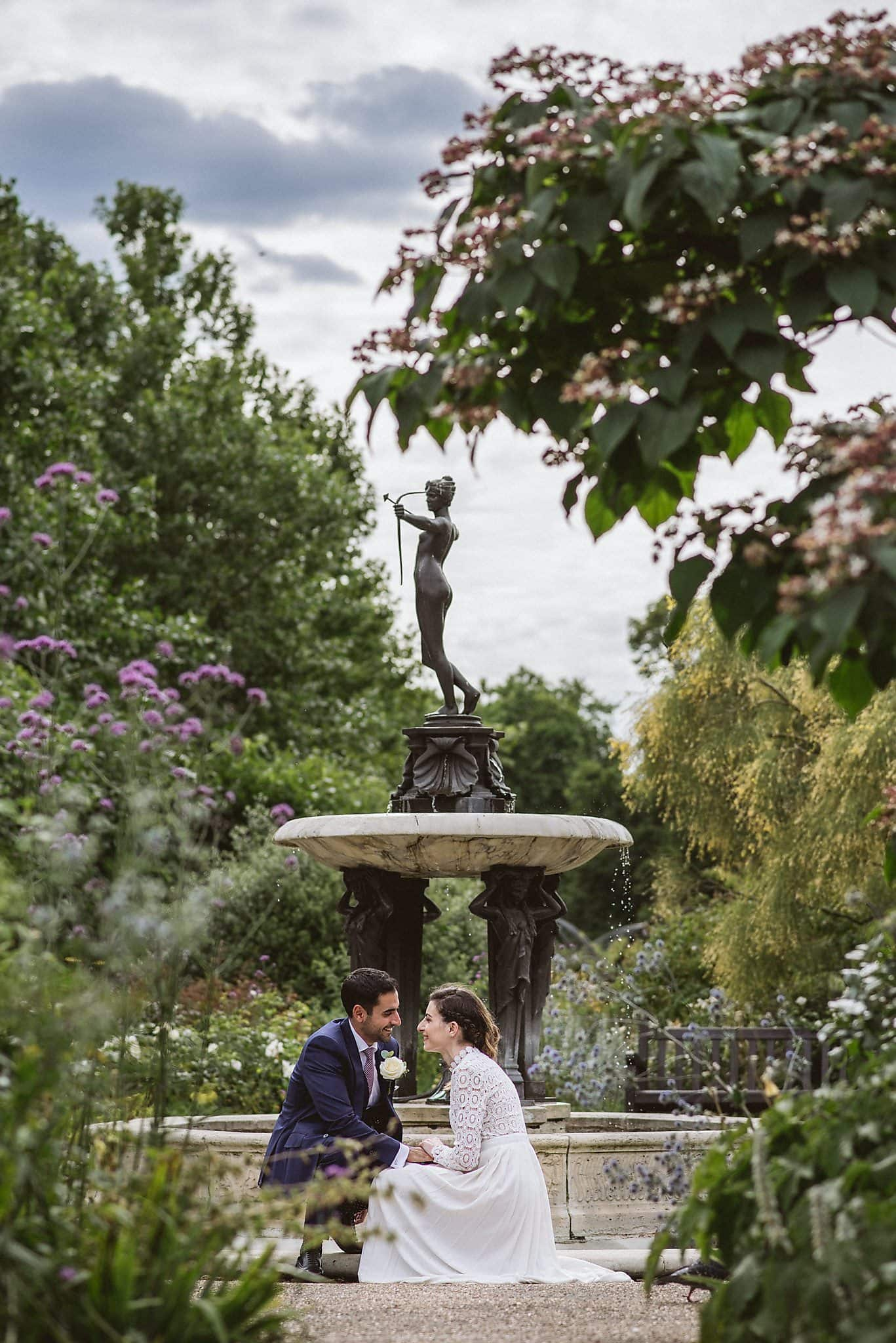 Bride and groom sit together by a fountain in Hyde Park
