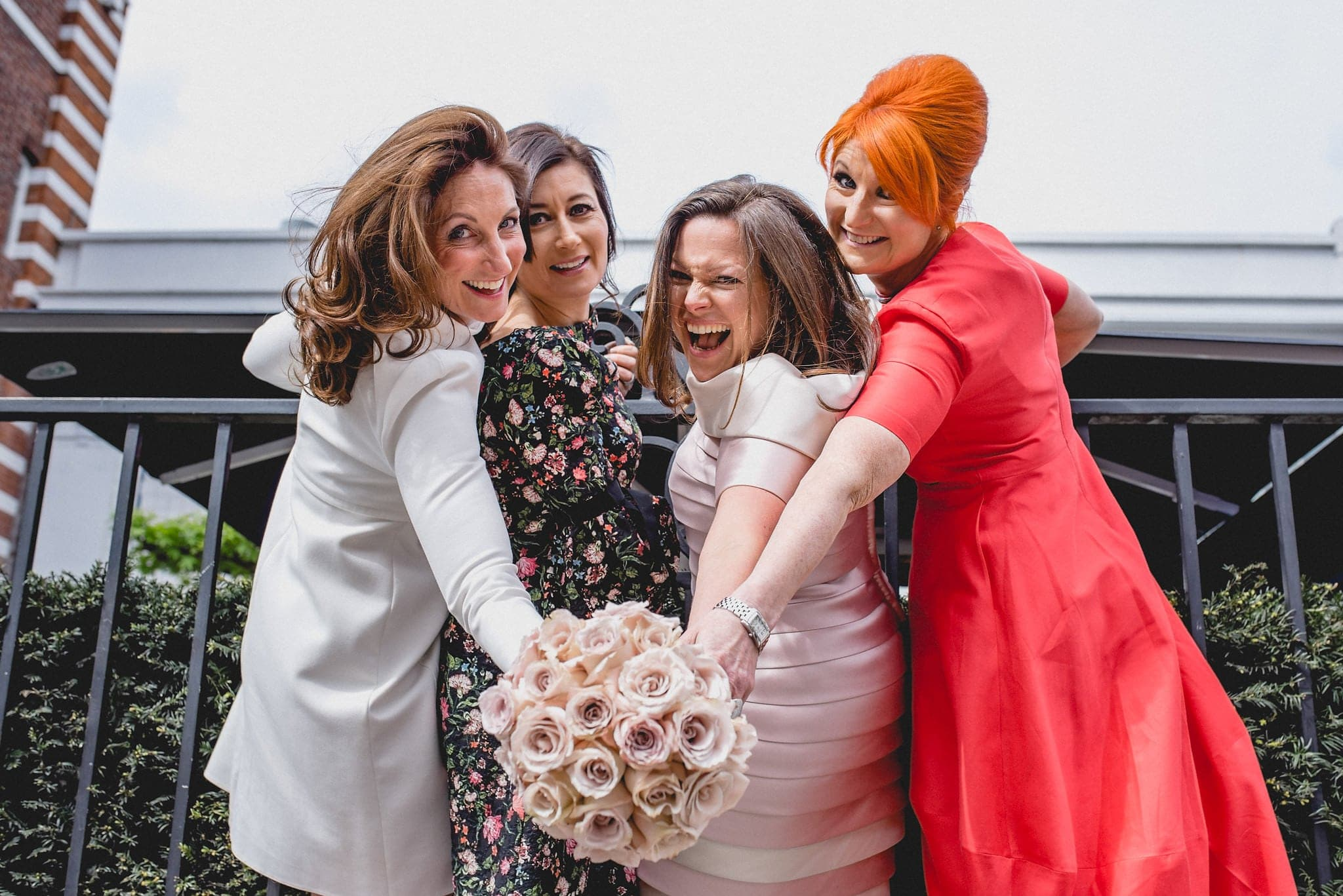 Bride and friends pose on railings of Chelsea venue