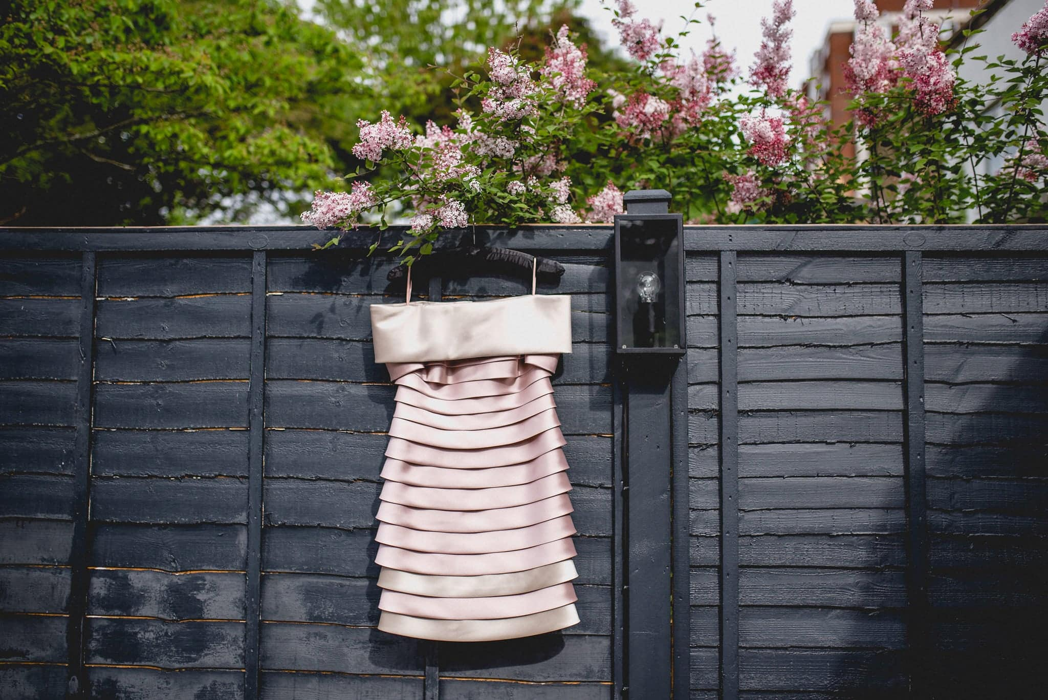 Alternative ruffled pink wedding dress hanging on black fence with lilac in the background