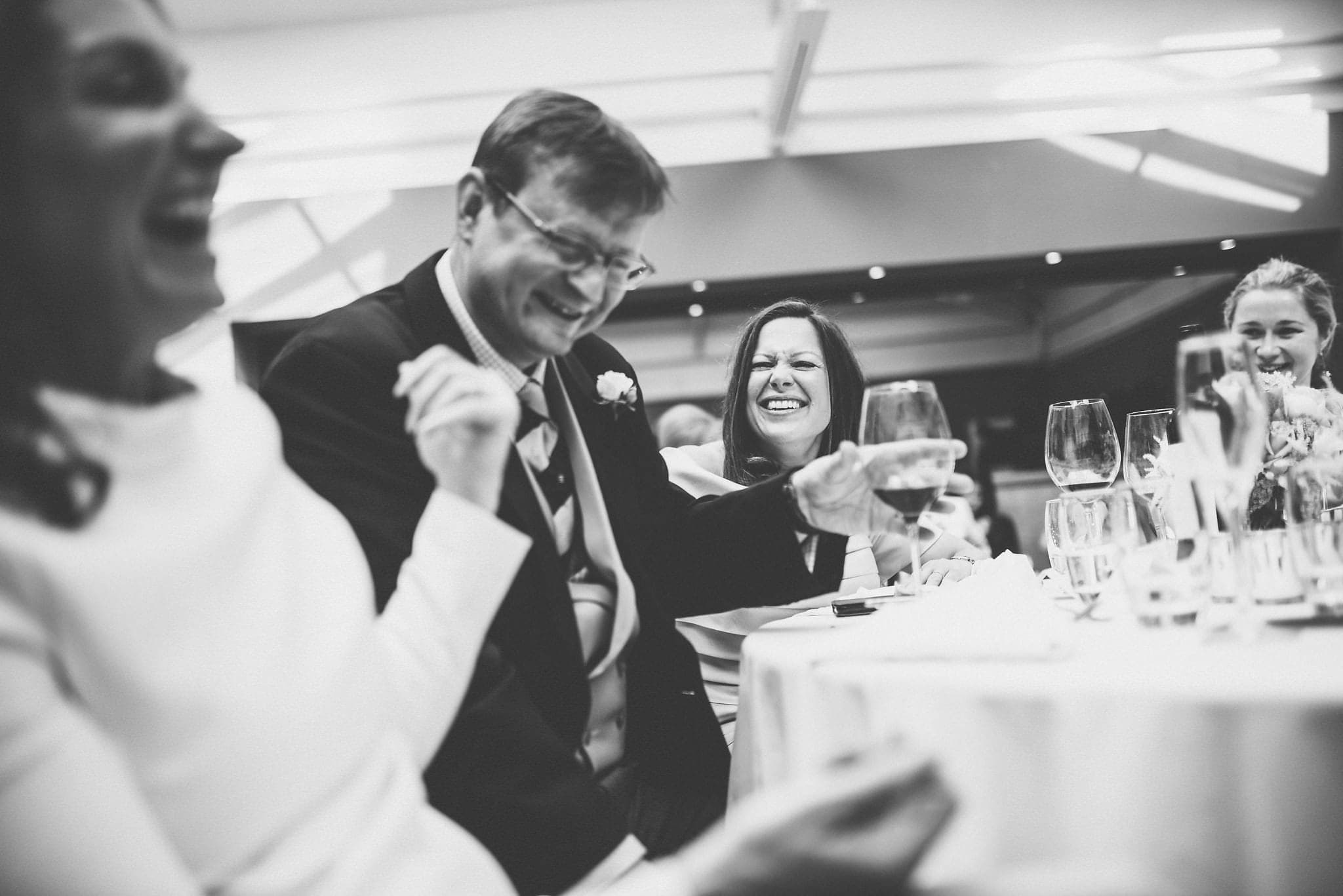 Bride, groom and guests laughing at reception