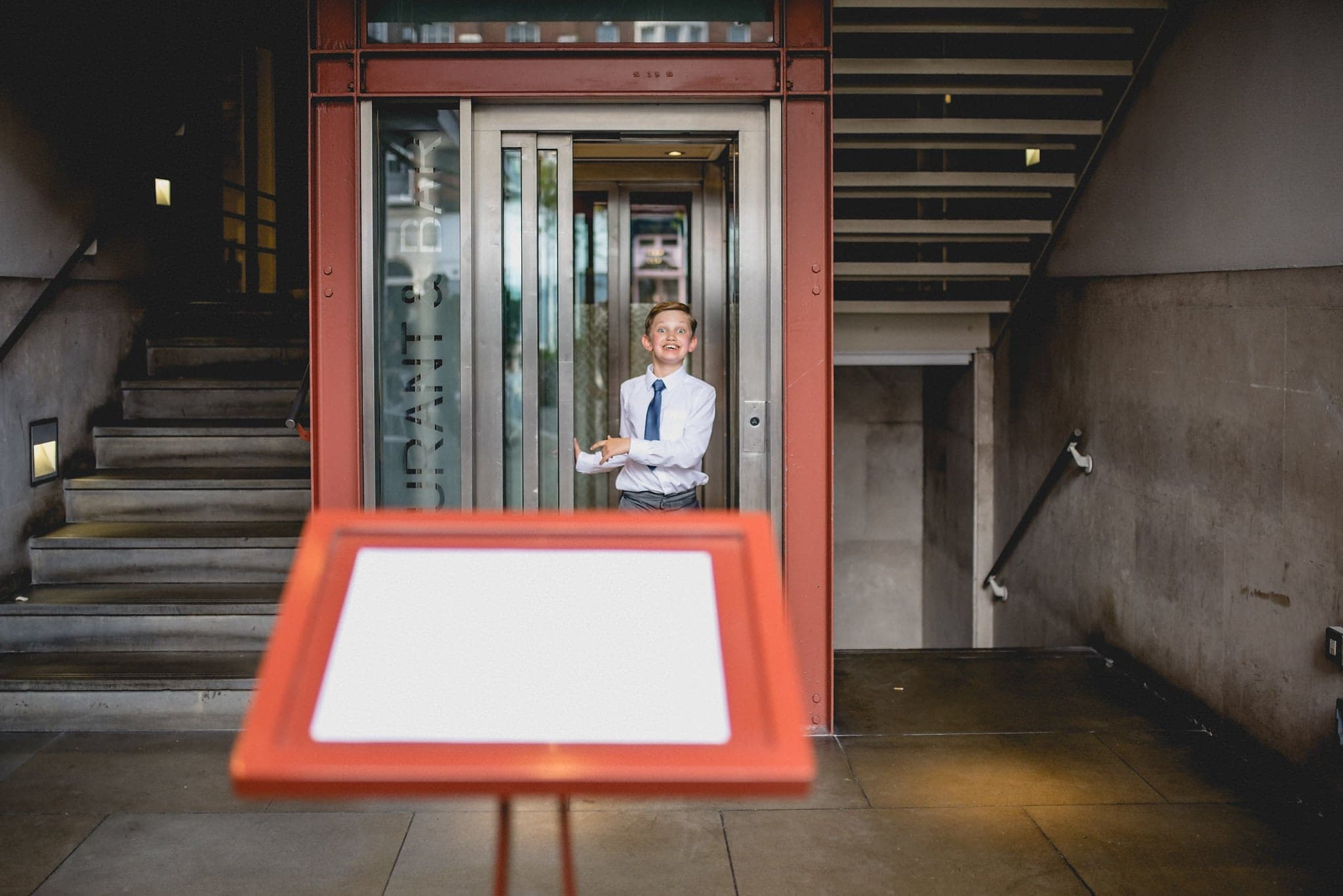Candid shot of boy in lift at The Bluebird wedding
