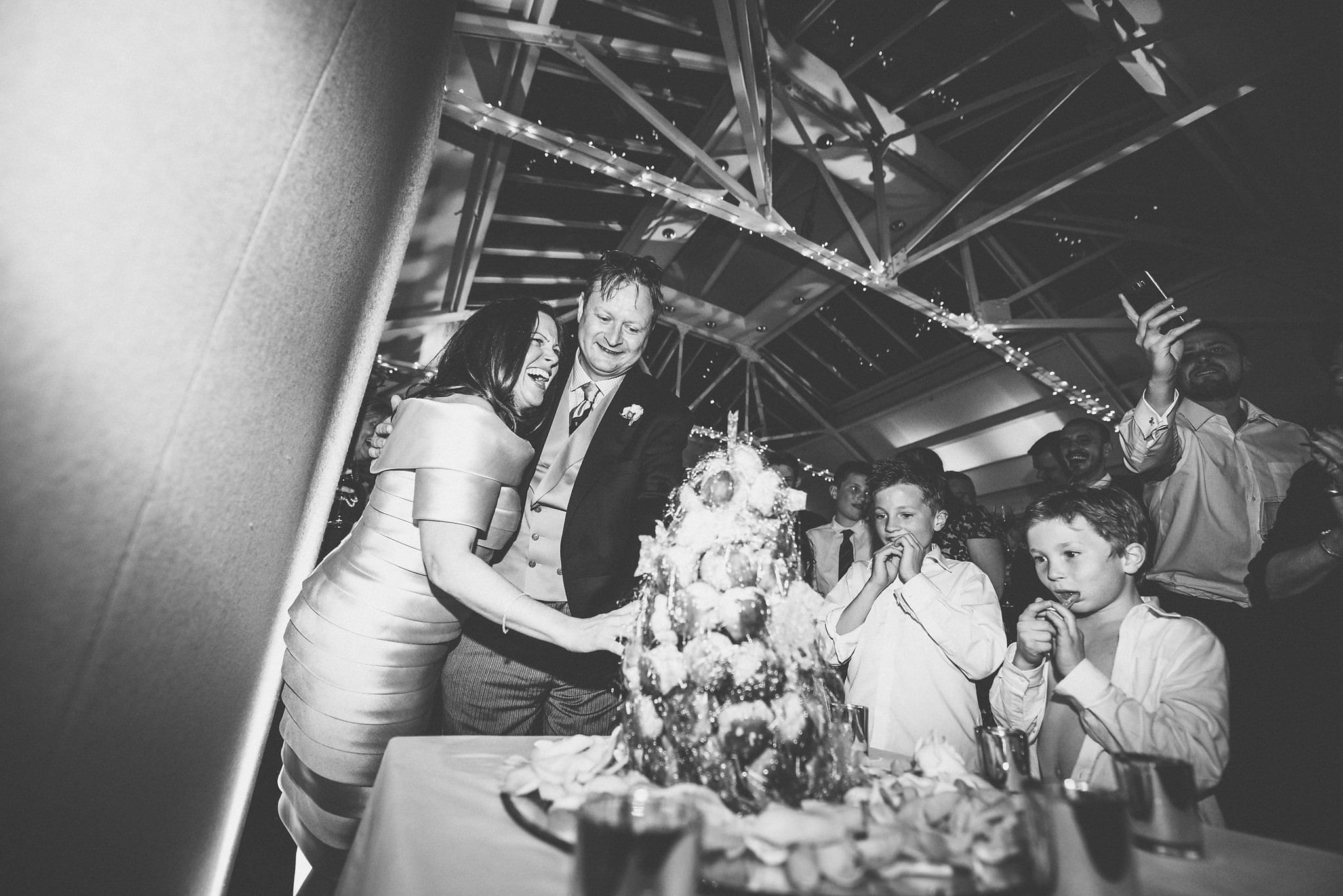 Black and white shot of bride and groom cutting into croquembouche