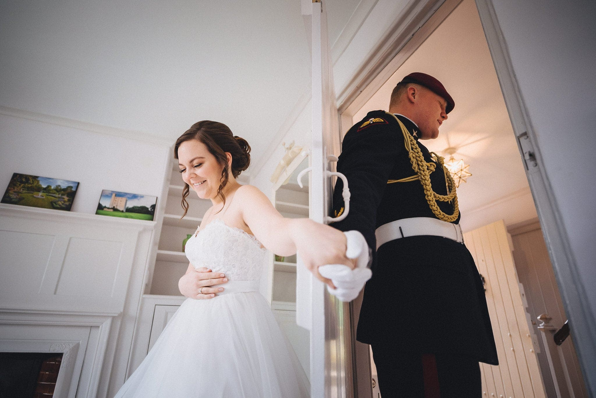 Bride and groom hold hands either side of door and say a prayer