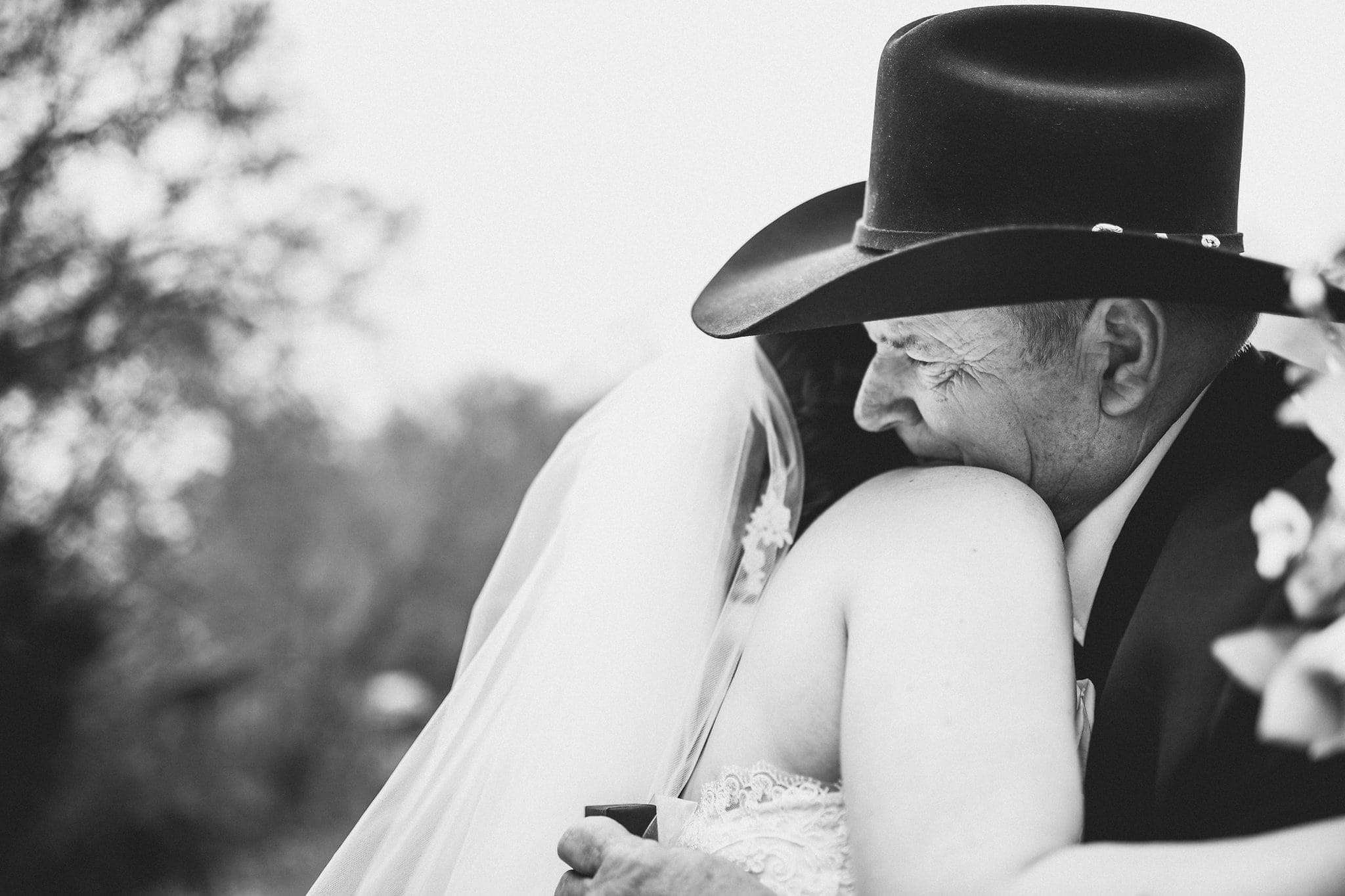 Black and white shot of father of bride in black stetson hugging bride