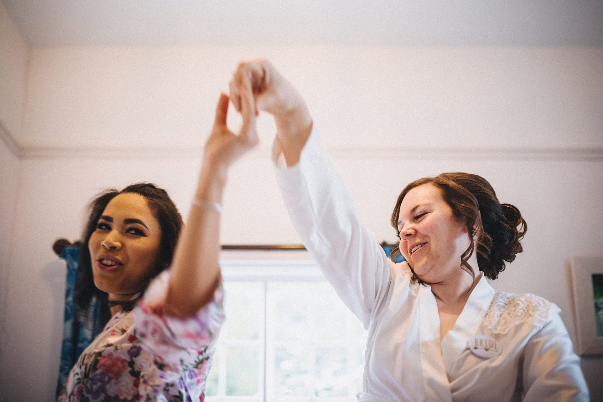 Bride and bridesmaid dance while getting ready for this Hedingham Castle wedding