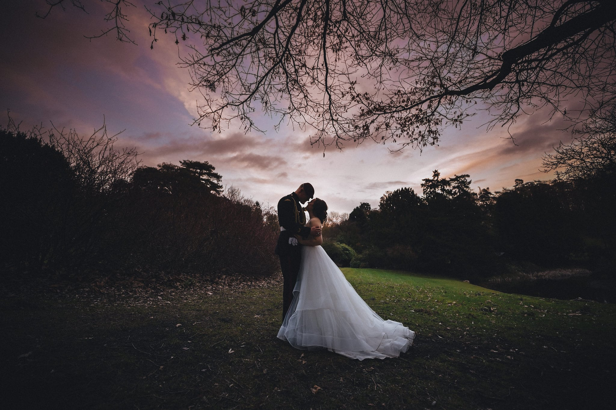Bride and groom hug at sunset at their International Military Hedingham Castle Wedding