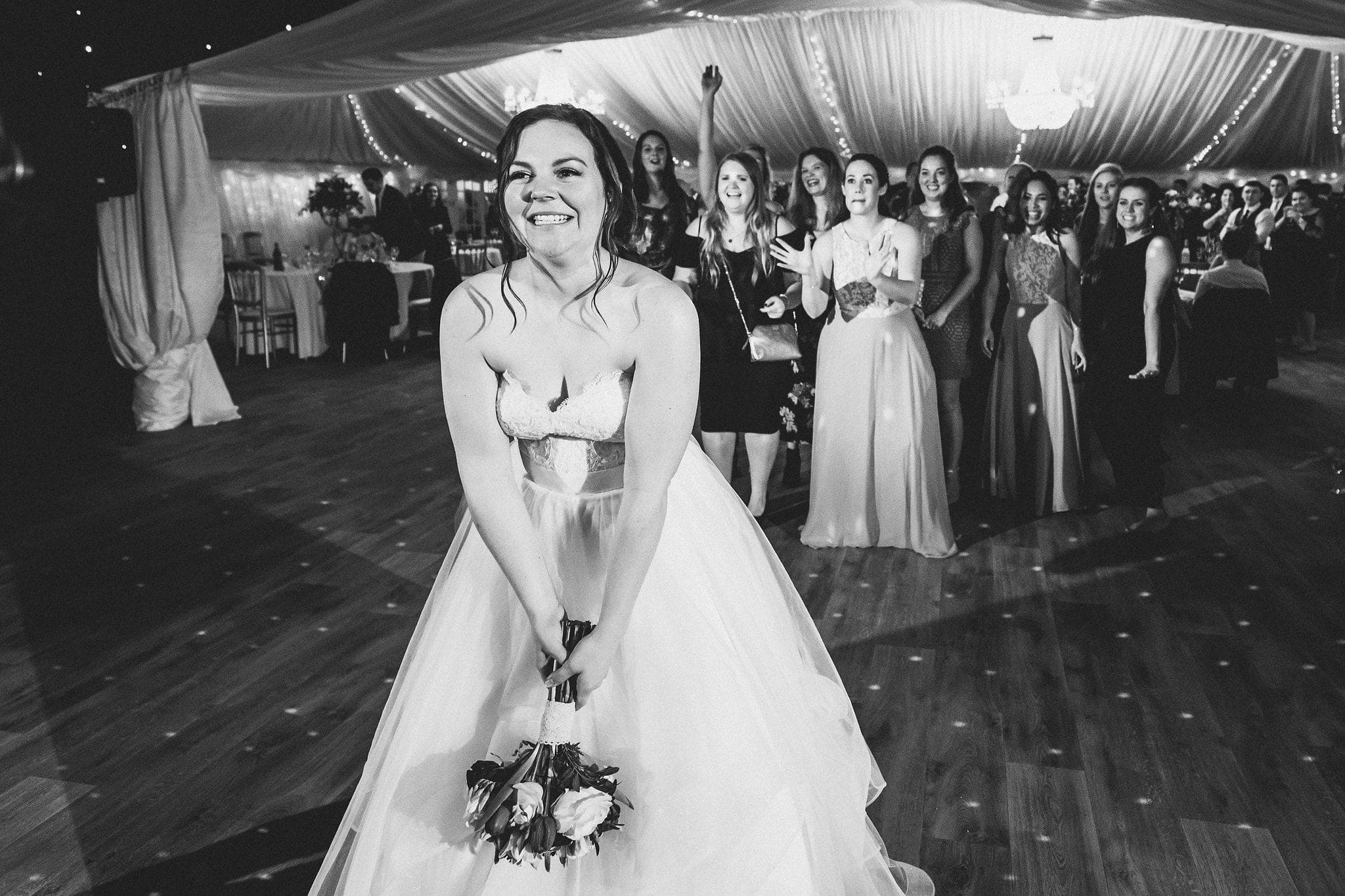 black and white shot of bride throwing bouquet
