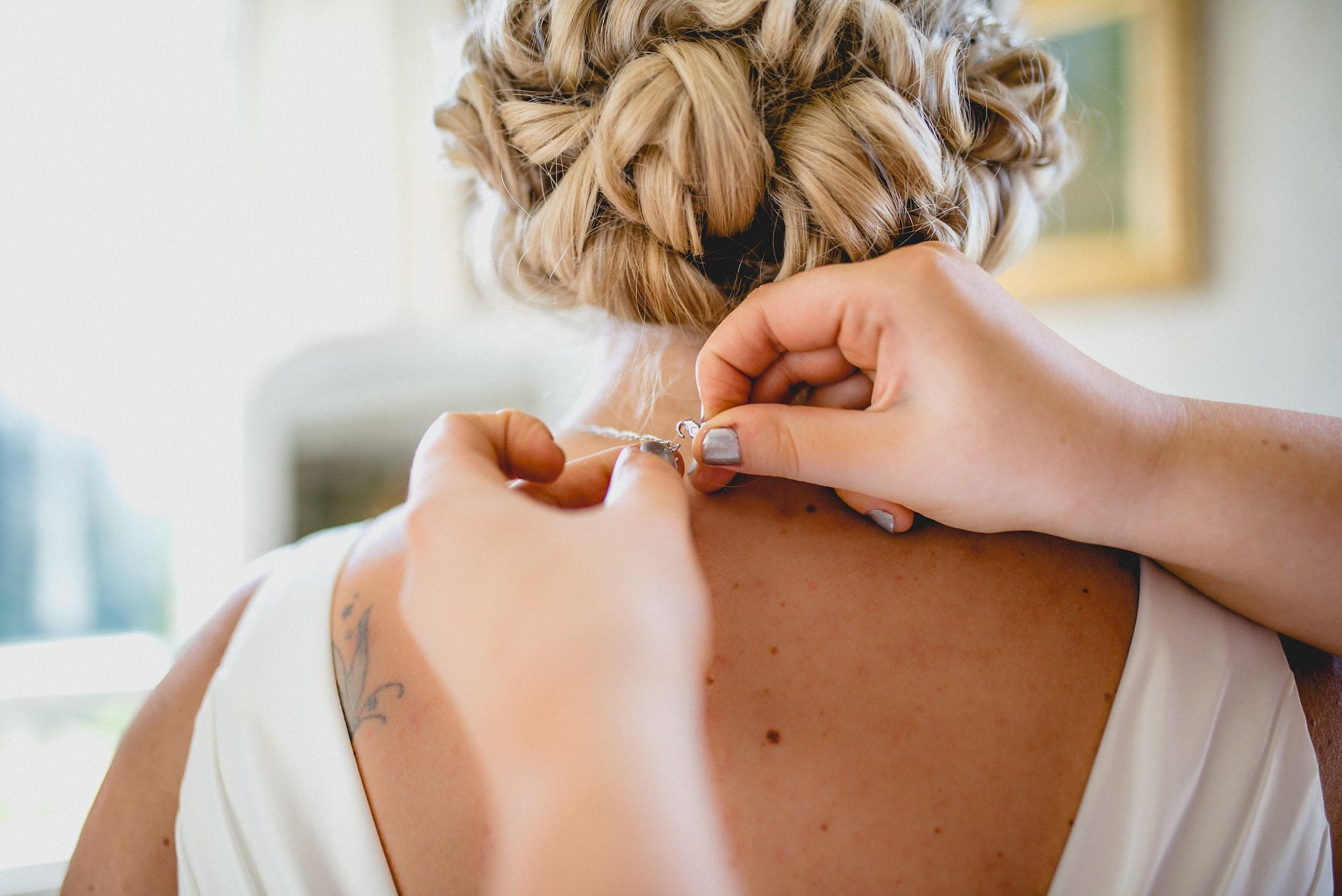 Bride has necklace fastened as she gets ready for her Shendish Manor wedding