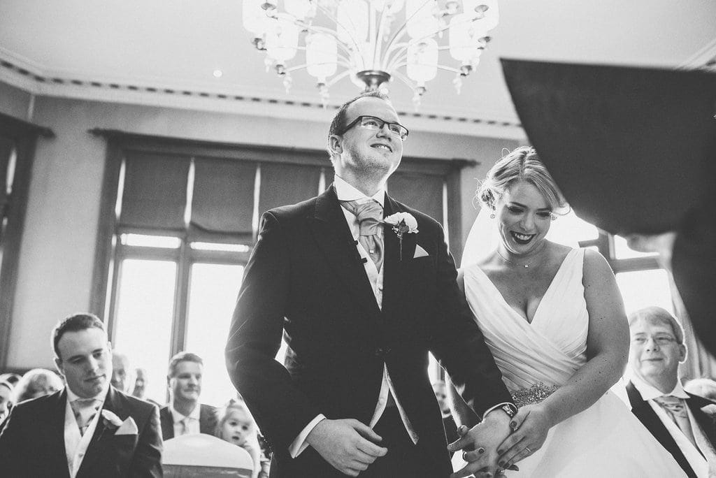 Black and white shot of bride and groom laughing together during their wedding ceremony