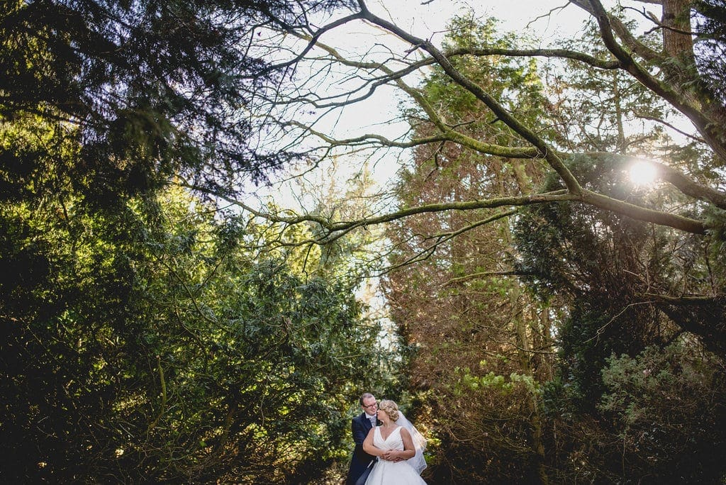 Bride and groom embrace in the woodland in the grounds of Shendish Manor