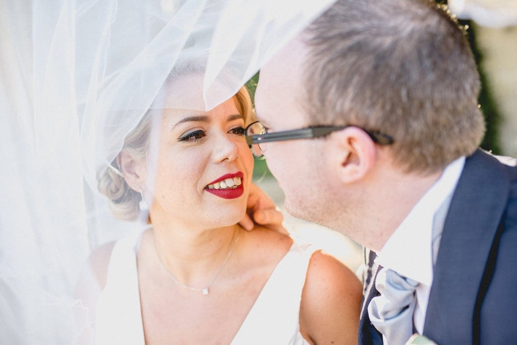Bride in red lipstick looks into groom's eyes. Veil billows around them.