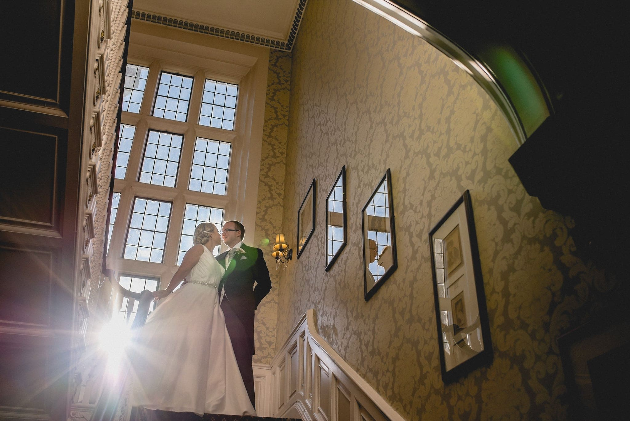 Bride and groom kiss at the top of a sunlit staircase