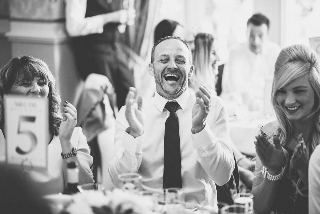 Black and white shot of guests laughing at wedding speech