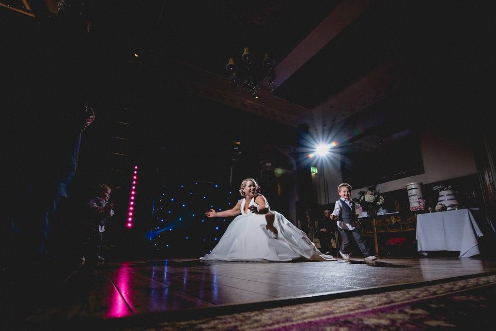 Bride crouches to dance with children on dancefloor at wedding