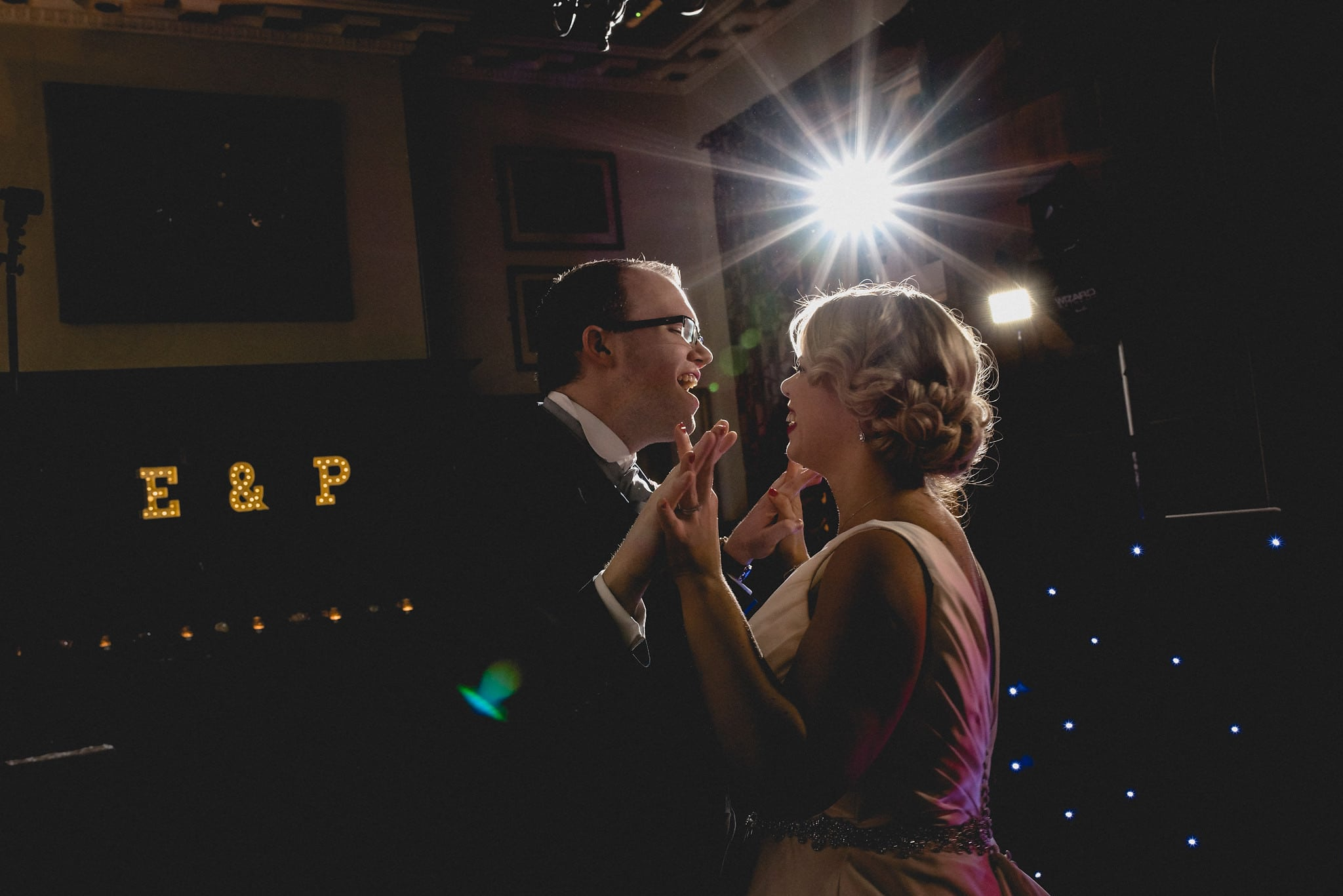 Bride and groom on dancefloor with light up initials in the background