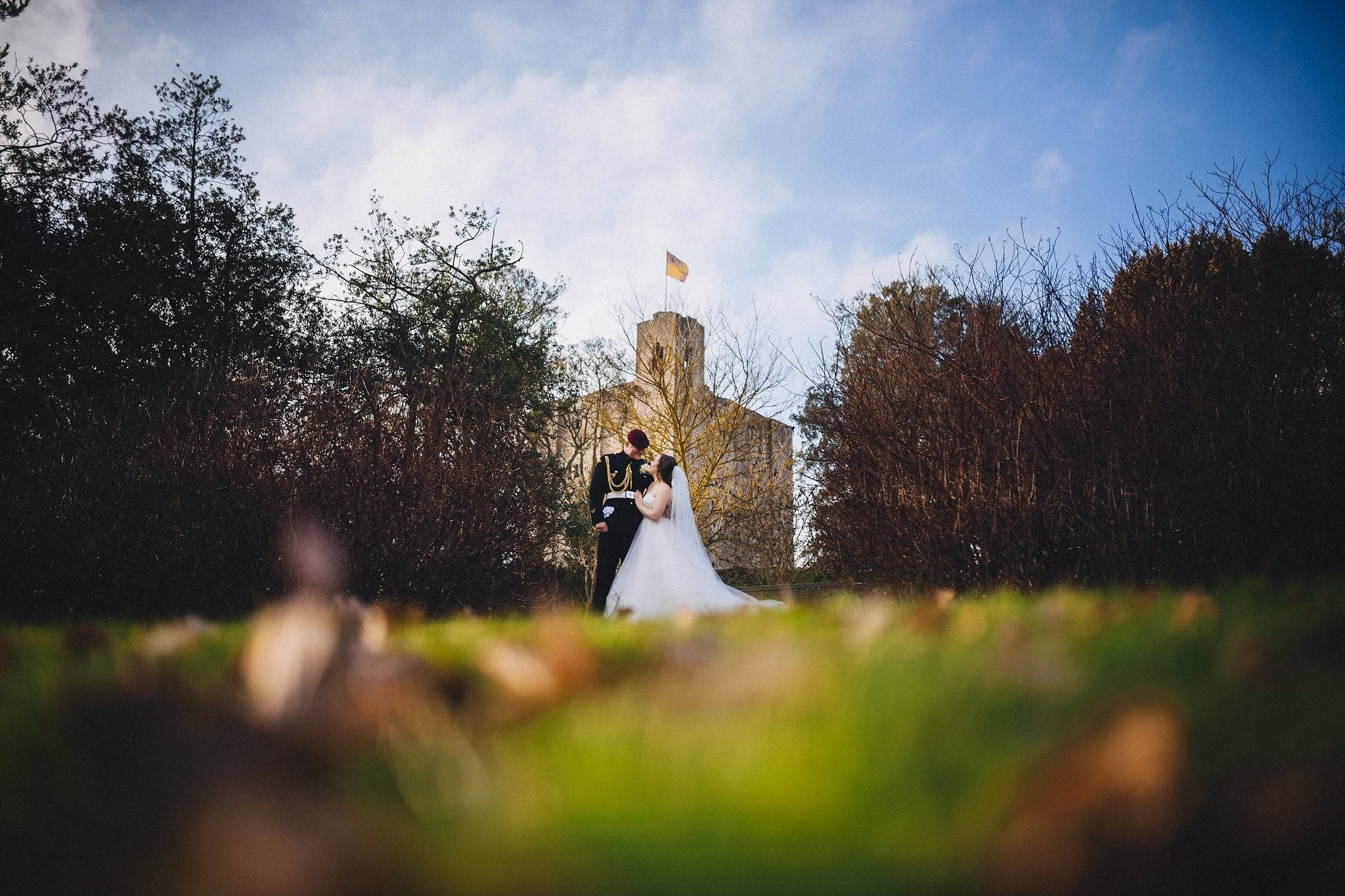 Bride in long veil and groom in military uniform at Hedingham Castle
