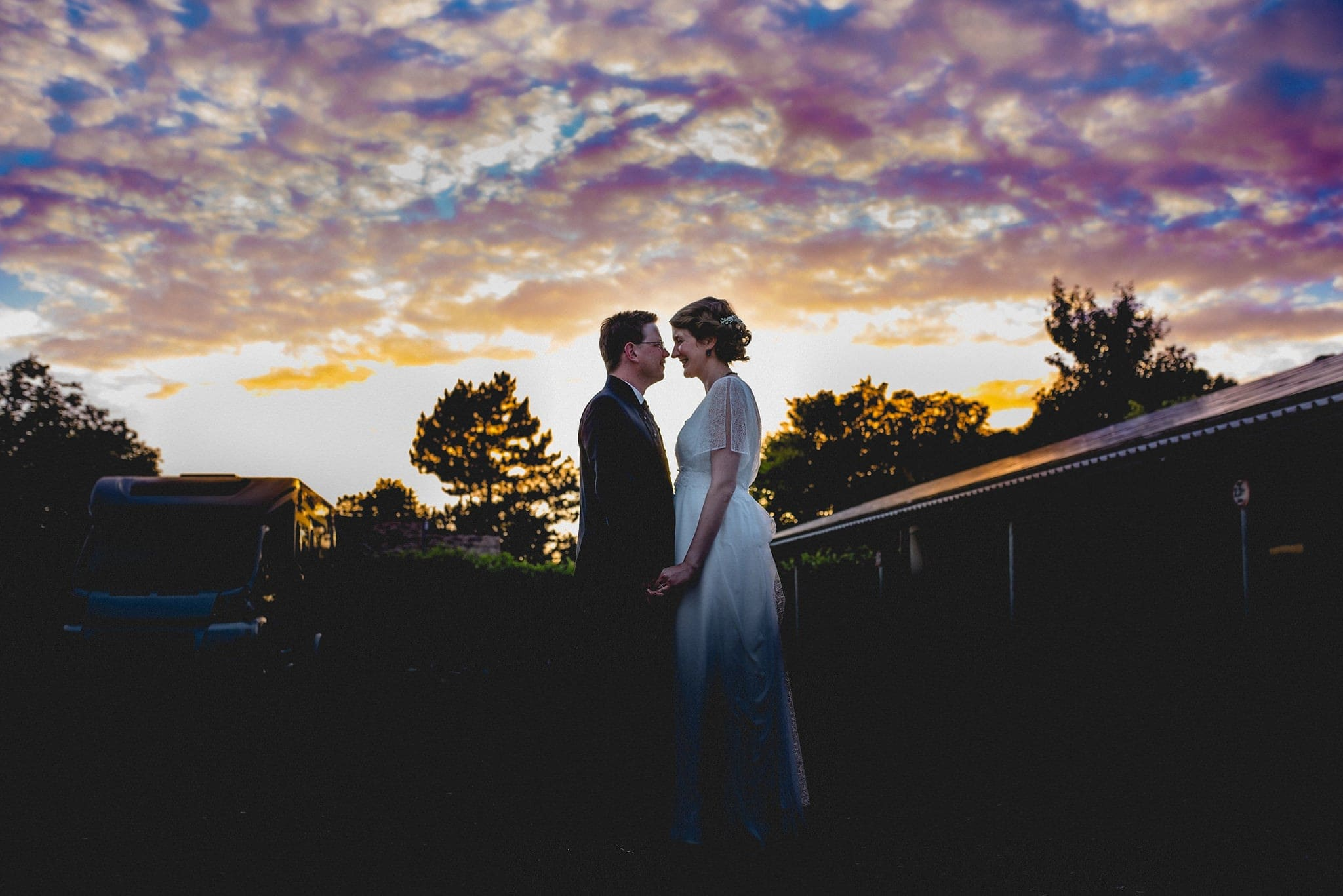 Bride and Groom standing in in front of a sunset sky at their Heartfelt Destination Wedding in Germany | Maria Assia Photography