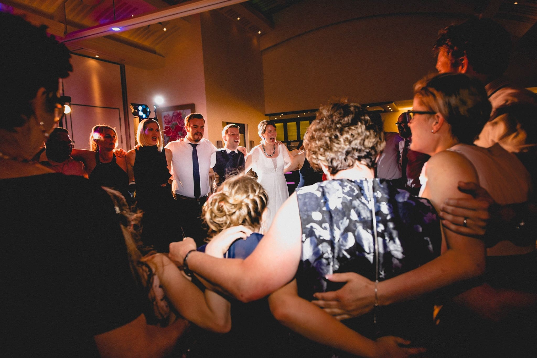 Bride, Groom and their wedding guests dancing the conga