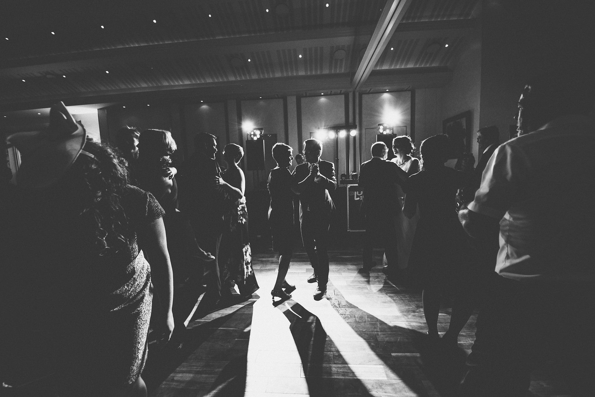 Groom dancing with his mother surrounded by wedding guests in a black and white silhouette