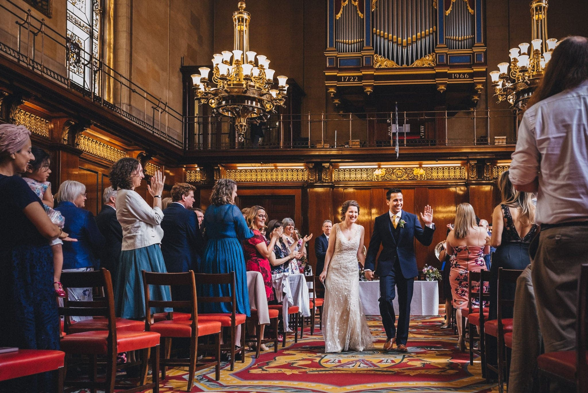 Bride and groom walk back down the aisle at Merchant Taylor's Hall