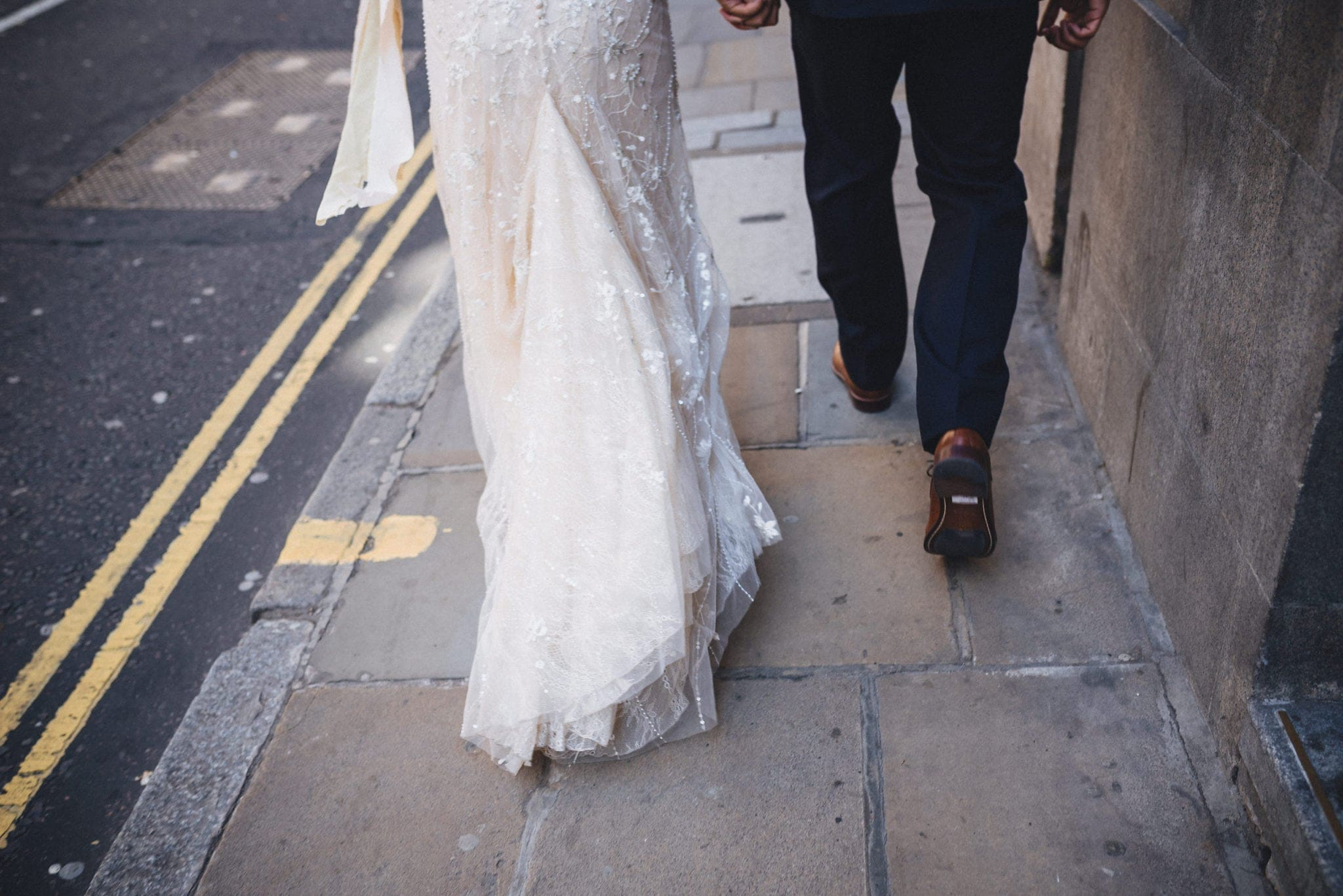 Close up of bride and groom's legs walking along London street