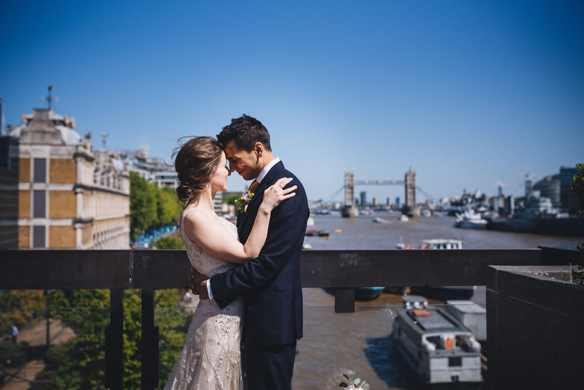 Bride and groom on bridge overlooking Tower Bridge